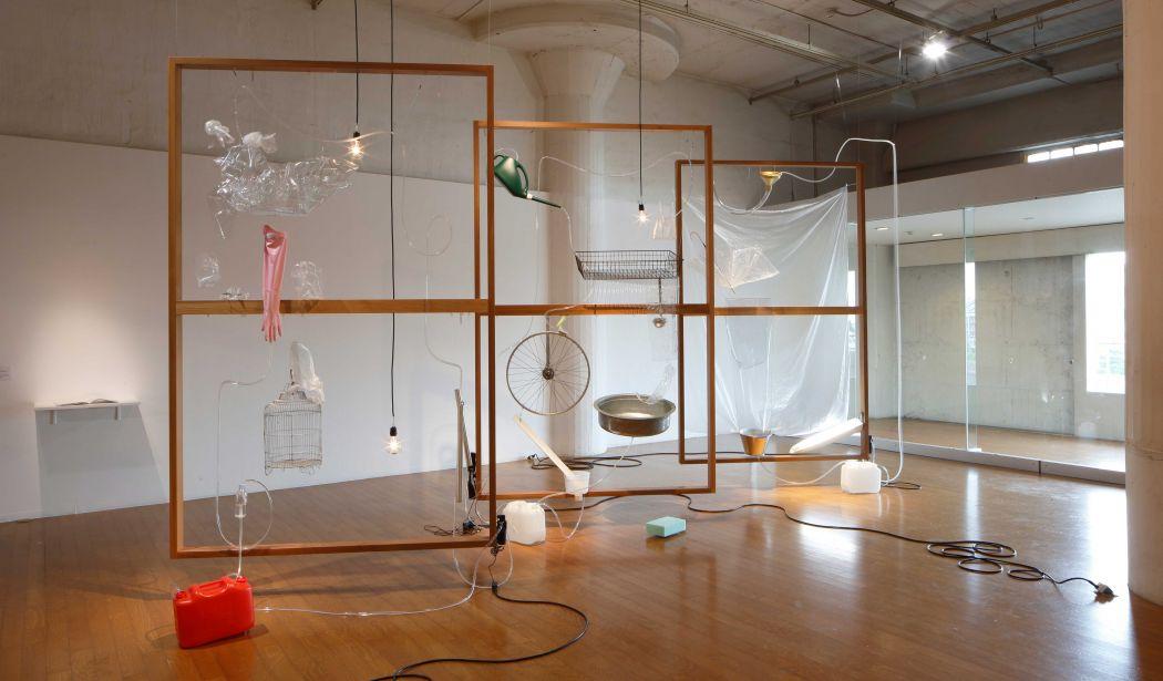 Yuko Mohri,  Moré Moré (Leaky): The Falling Water Given #1-3 , 2015, wood, umbrella, hose, PET bottles, rubber glove, bucket, wheel, duster, sponge, pump, acrylic resin, etc. Installation view at Nissan Art Award 2015 Exhibition. Photo by Keizo Kioku