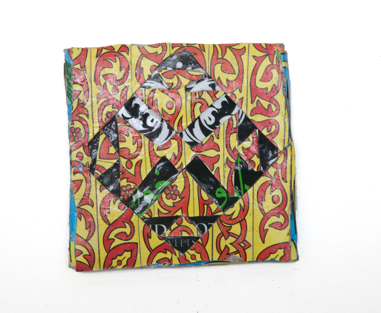 Michael Rakowitz   May The Obdurate Foe Not Stay in Good Health - Gilded glass tile with cross-shaped motifs, Maarat al-Nu'man , 2016 Syrian and other Middle Eastern packaging and newspapers, glue 3.54 x 3.54 inches 9 x 9 cm Courtesy of the artist and Jane Lombard Gallery, NY