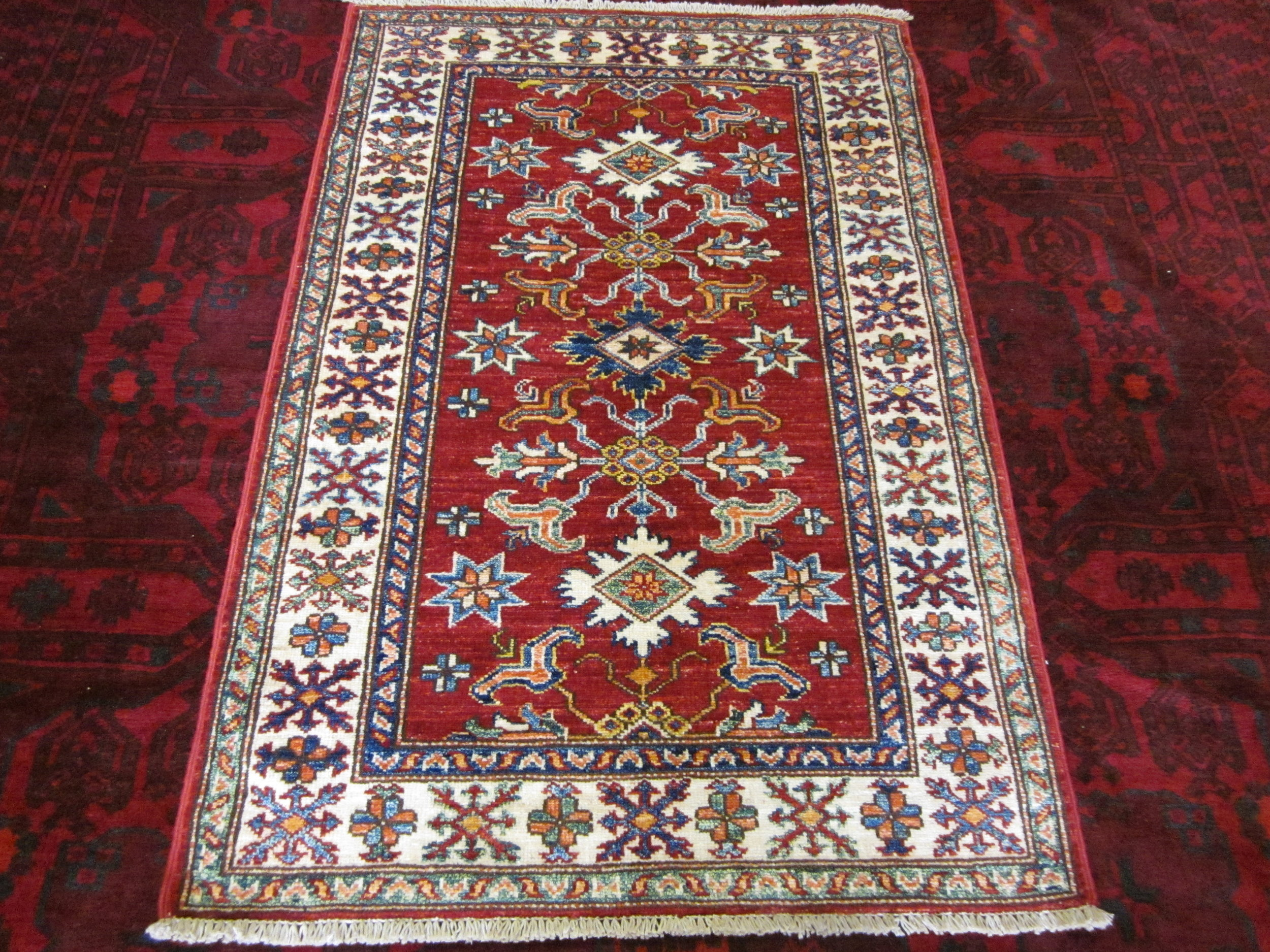"#46) 2'8"" x 4'1"" Red Kazak rug. Sold."