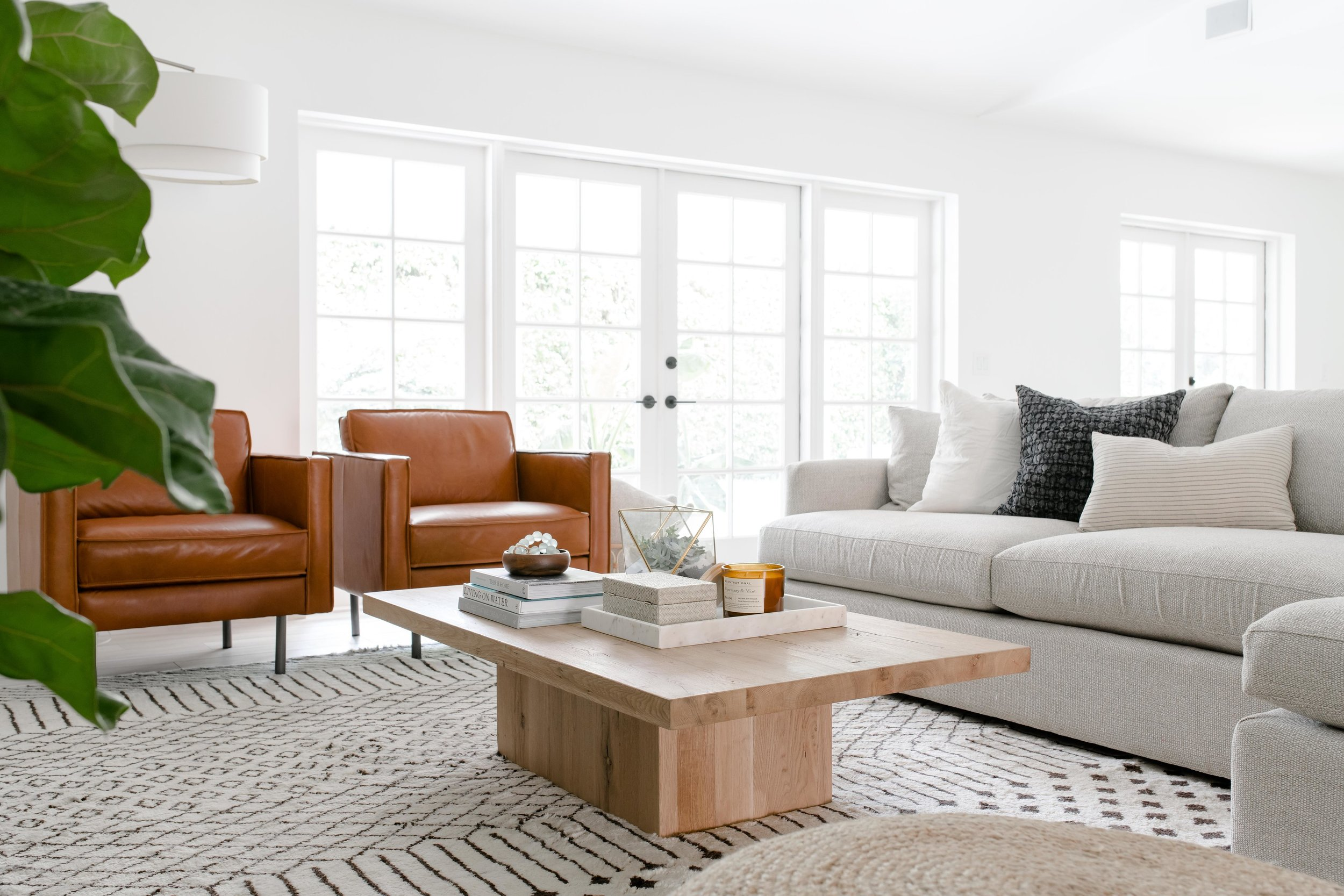 modern living room with neutral sectional, warm wooden coffee table, leather accent chairs, wood tile floors - the habitat collective - project casinha linda