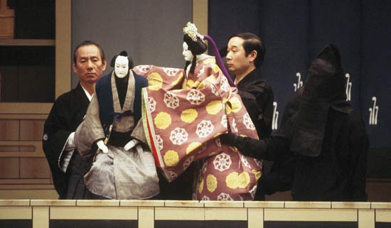 bunraku in performance, with master and APPRENTICE (hooded) puppeteers