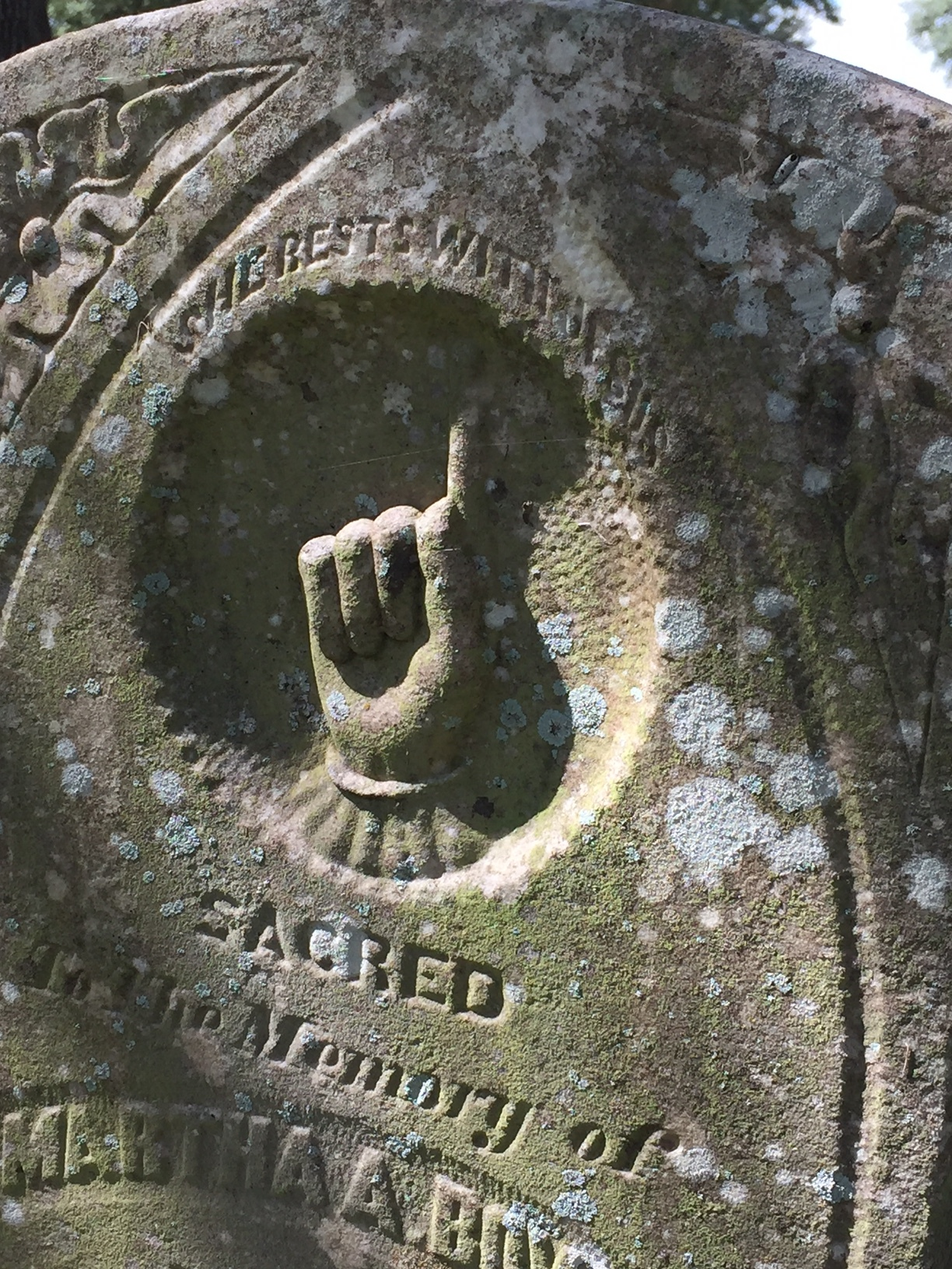 The hand pointing upward as a symbol for heaven is a common one found throughout the cemetery