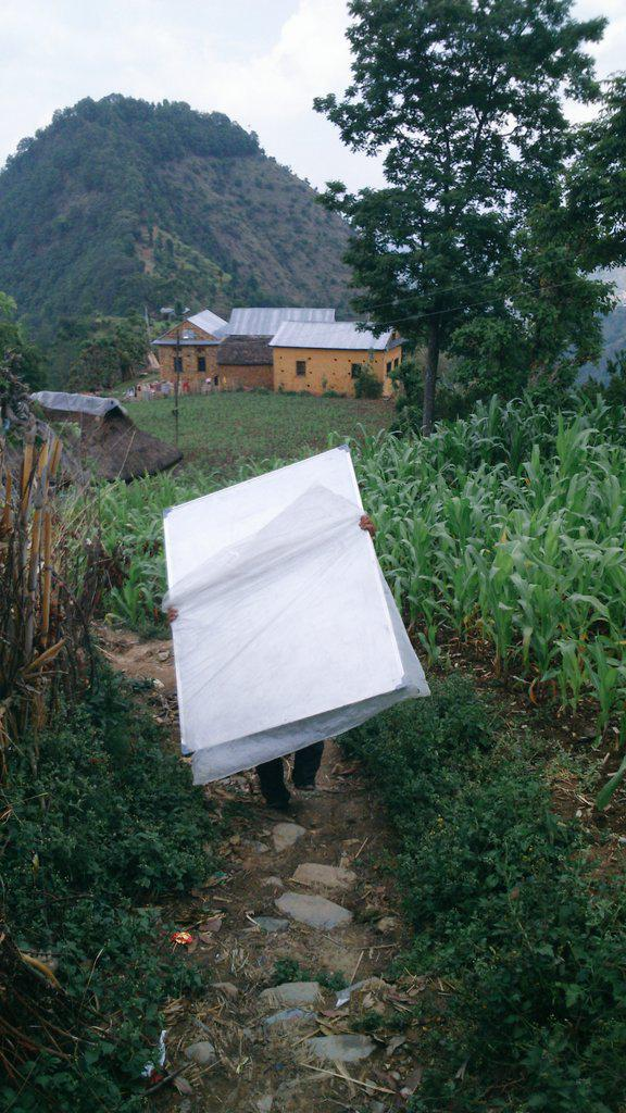 A CYF volunteer delivering whiteboards to the school.  Man  has been able to continue teaching classes using school supplies and temporary classrooms funded by CYF donors.