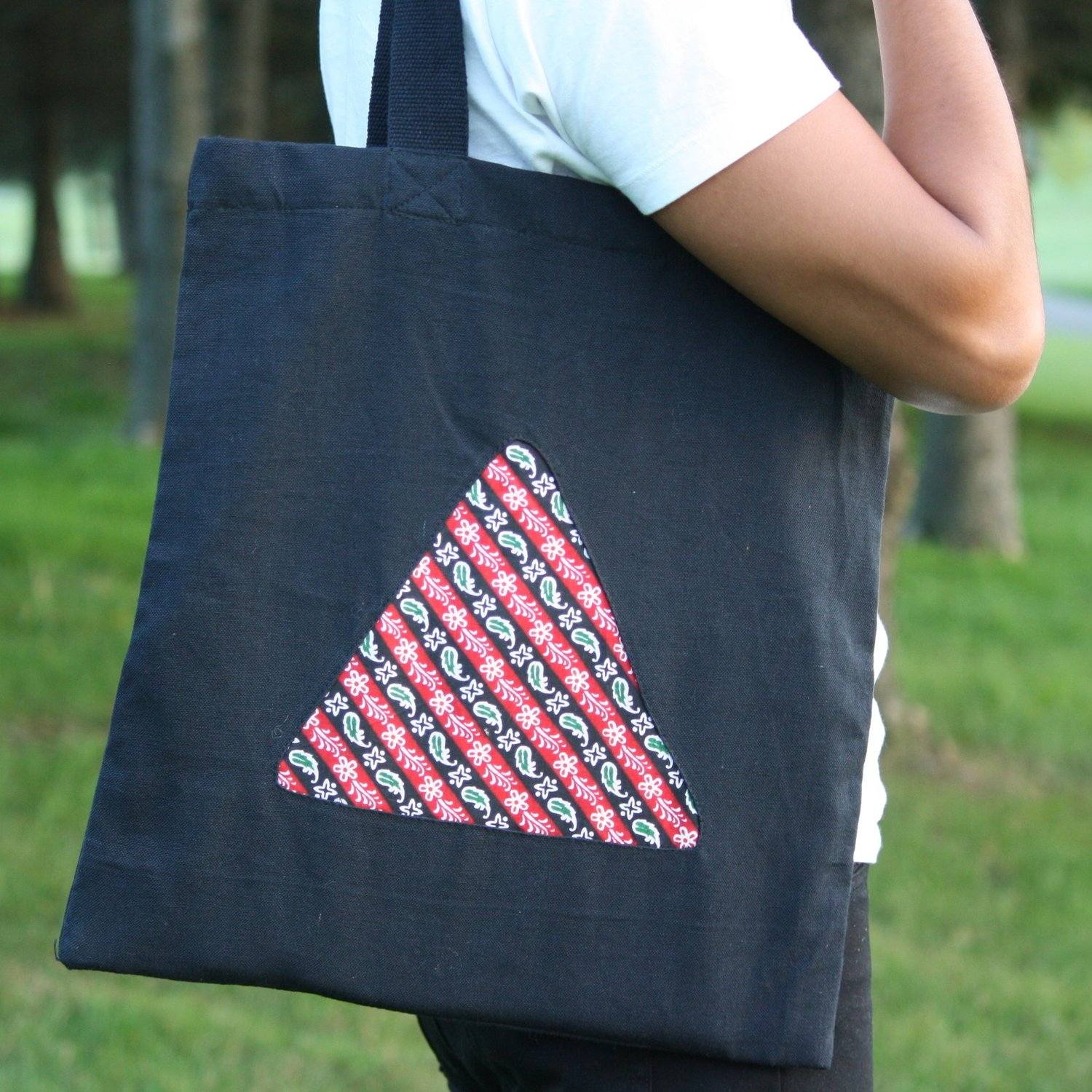 The Triangle Tote , $15  Our signature canvas triangle bag could be your new go-to tote! Durable canvas on the outside, nylon on the inside: perfect for groceries or beach trips. Choose your favorite Dhaka pattern to show through the triangle cutout.