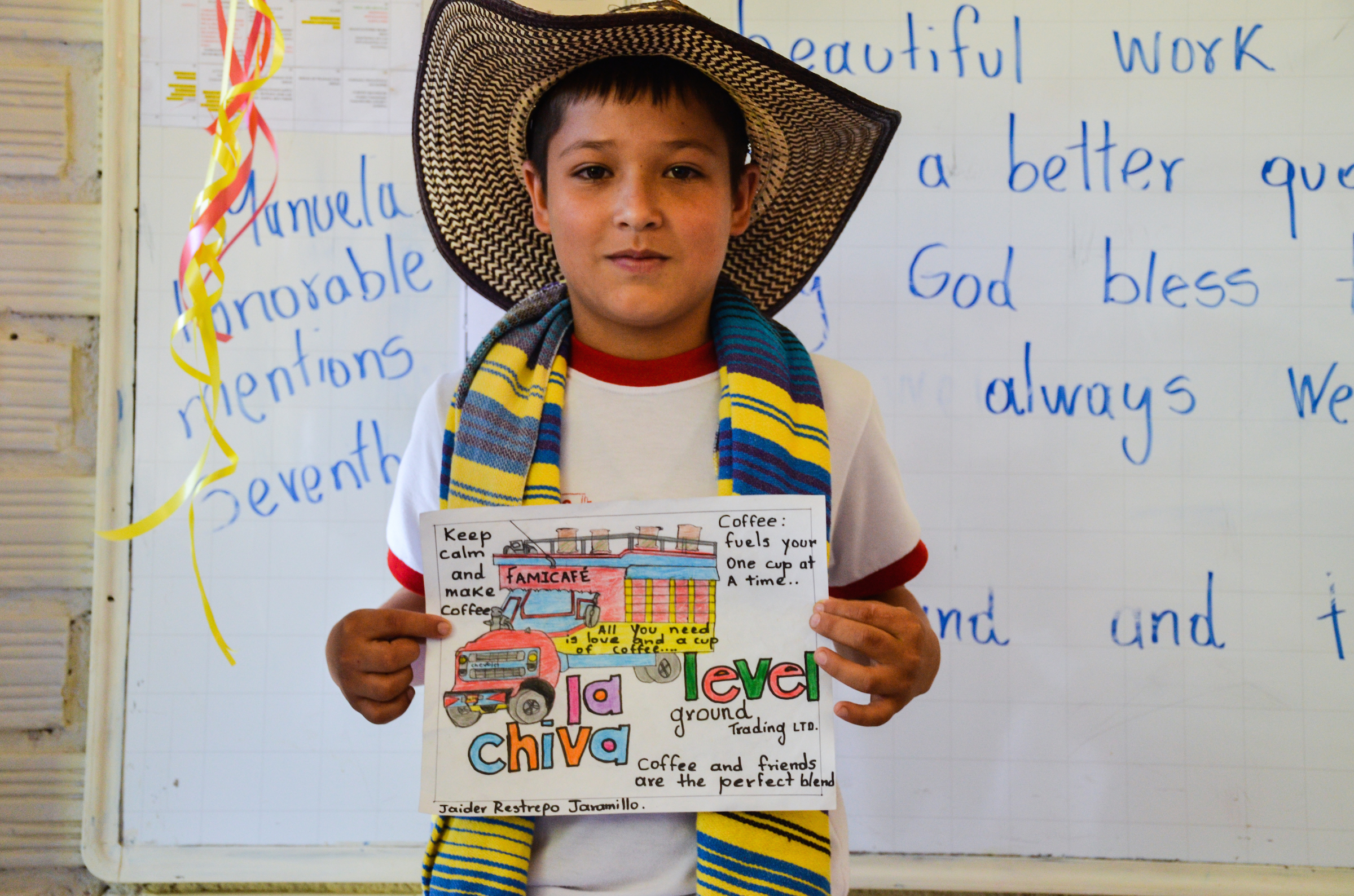 A student displays his welcome poster for Level Ground staff on a school visit.