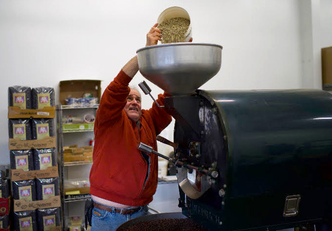 Michael pours beans into the roaster.