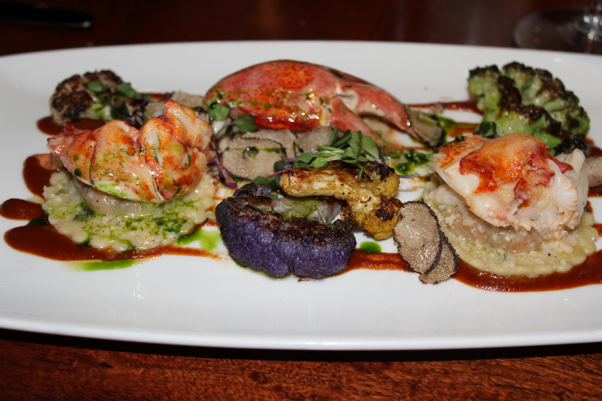 Brandy-Vanilla Poached Maine Lobster with Lobster and Parmesan Raviolis, Charred Rainbow Cauliflower, Lobster Beurre Blanc, and Truffles.