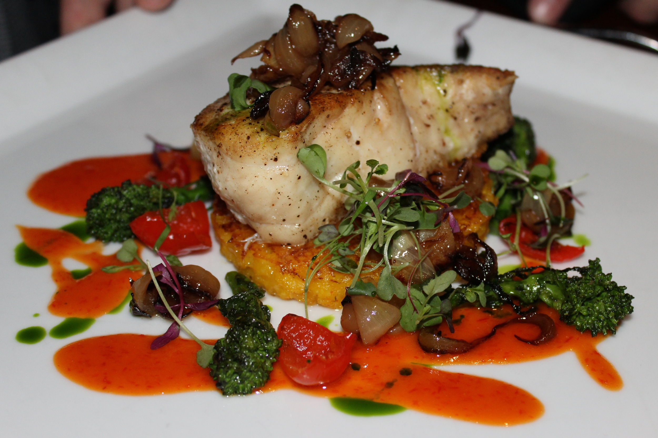 Seared Blue Nose Sea Bass with Crispy Saffron Parmesan Risotto Cake, Rapini, Cipollini Onions, and Peppadew Pepper Reduction