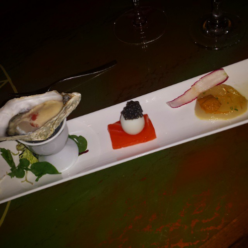 Oyster with mignonette, sake-cured salmon with quail egg and caviar, and scallop crudo with uni.