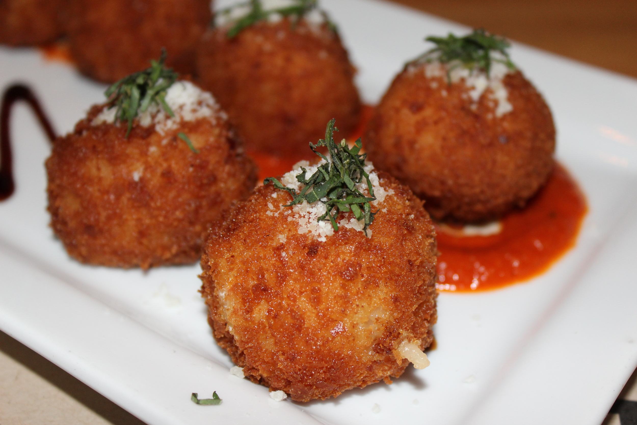 Arancini filled with house-pulled mozzarella with pomodoro and balsamic reduction
