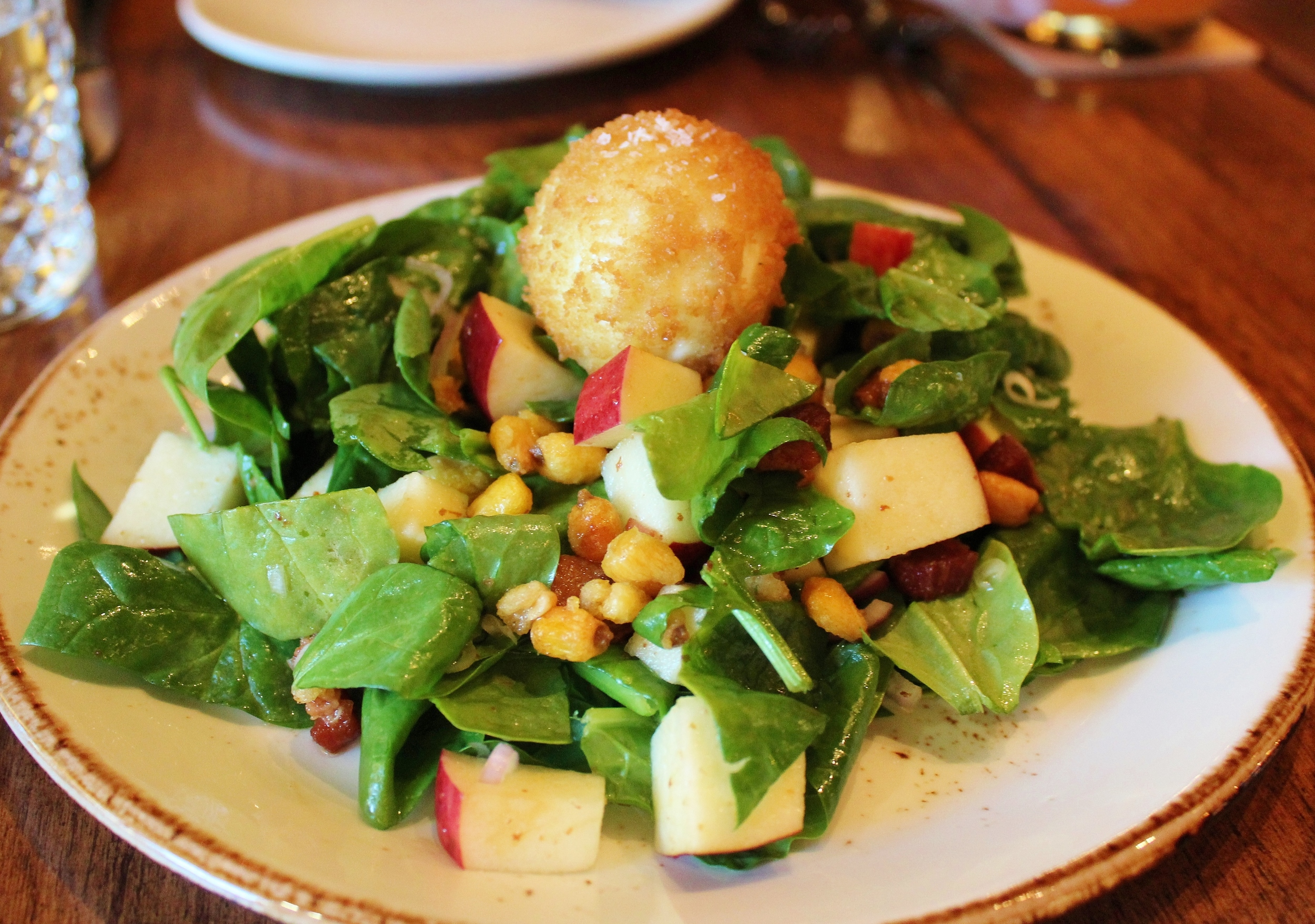 Spinach salad with crispy soft-boiled egg, apple, shallots, corn nuts, bacon vinaigrette