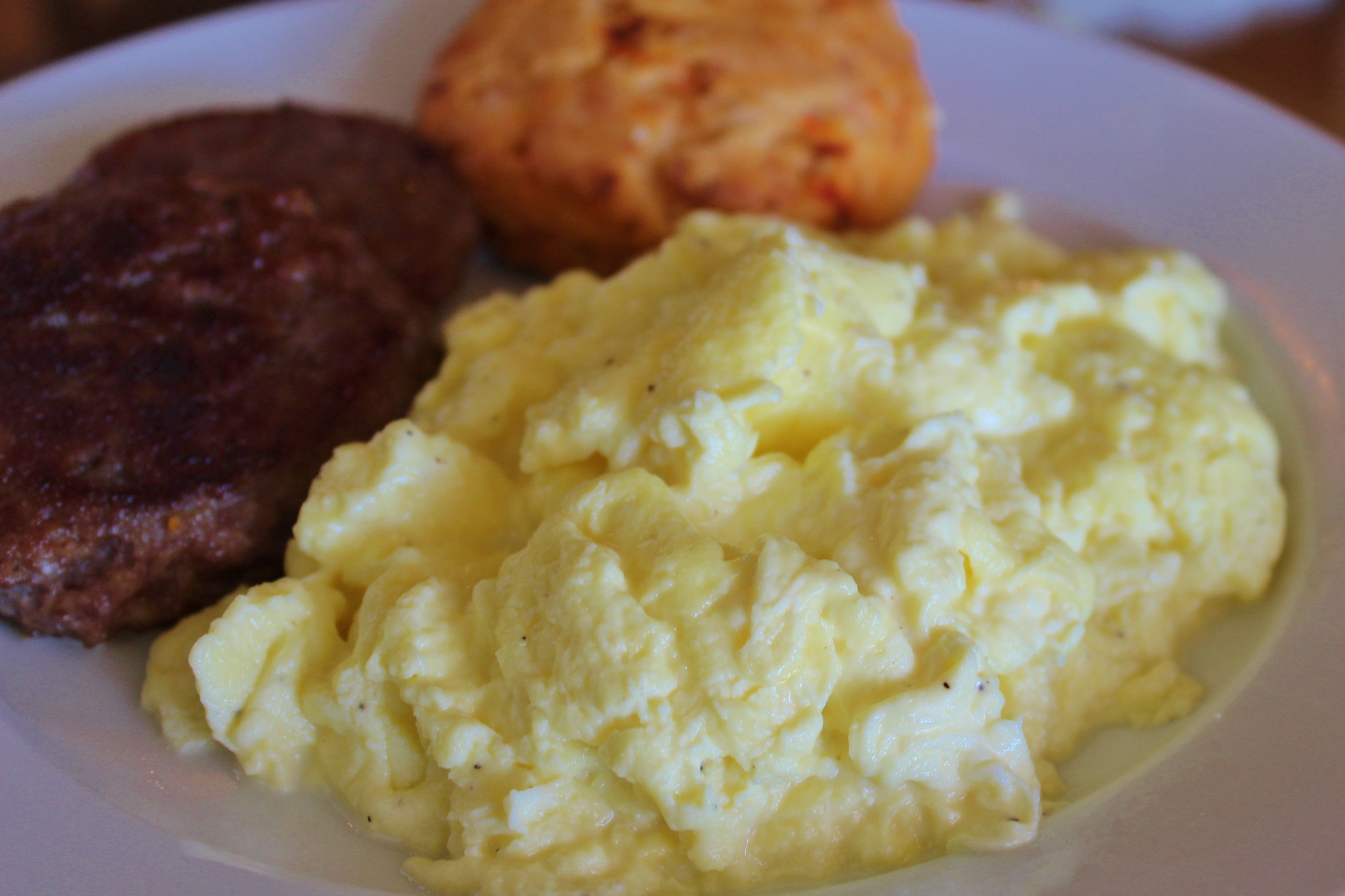 Scrambled eggs with maple sausage patties and a pimento cheese biscuit.