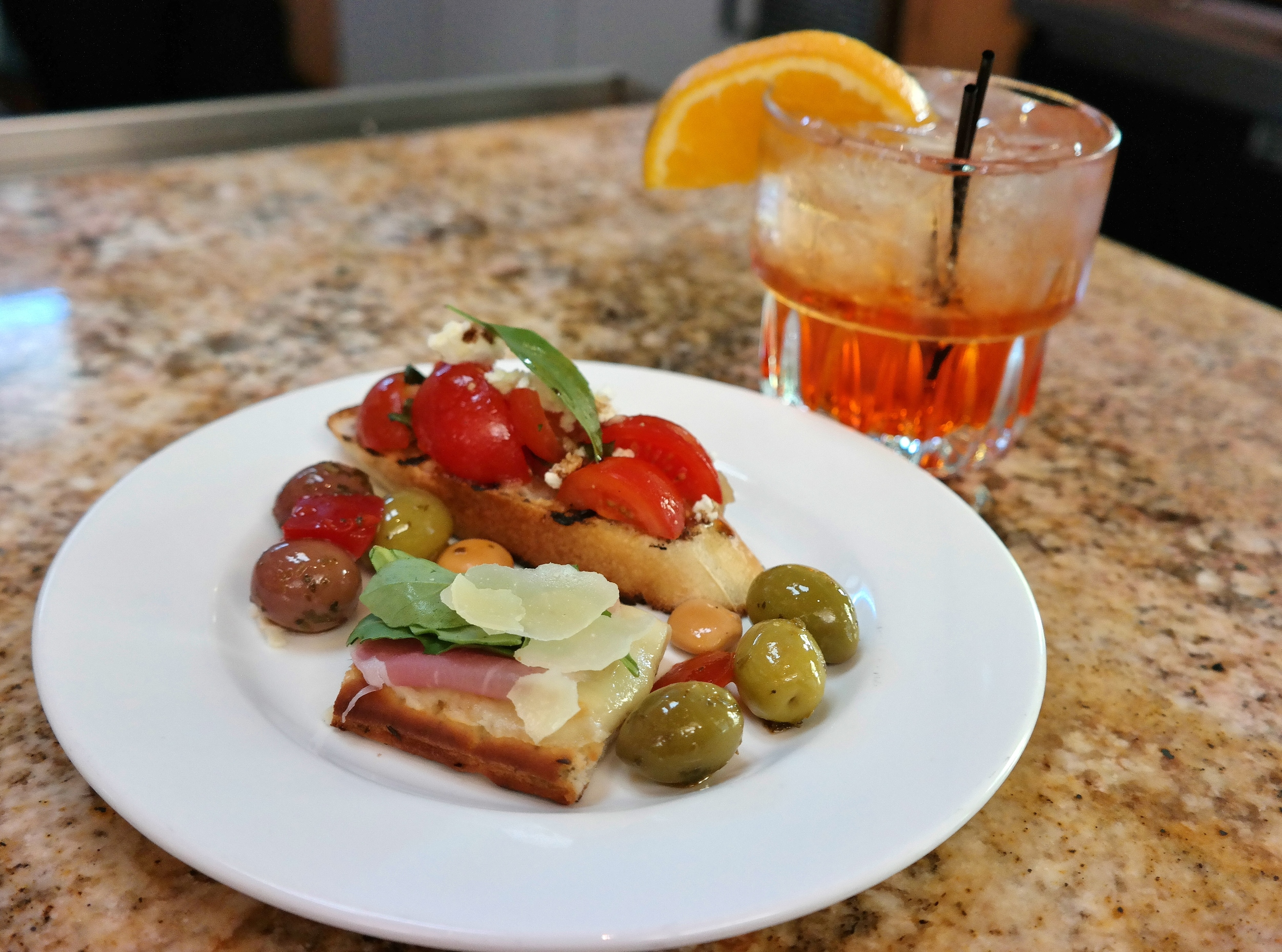 New-Groni (Bulldog gin, white vermouth, fruit infused-Aperol, orange bitters) with bruschetta, olives, pickled lupini beans, and prosciutto flatbread.