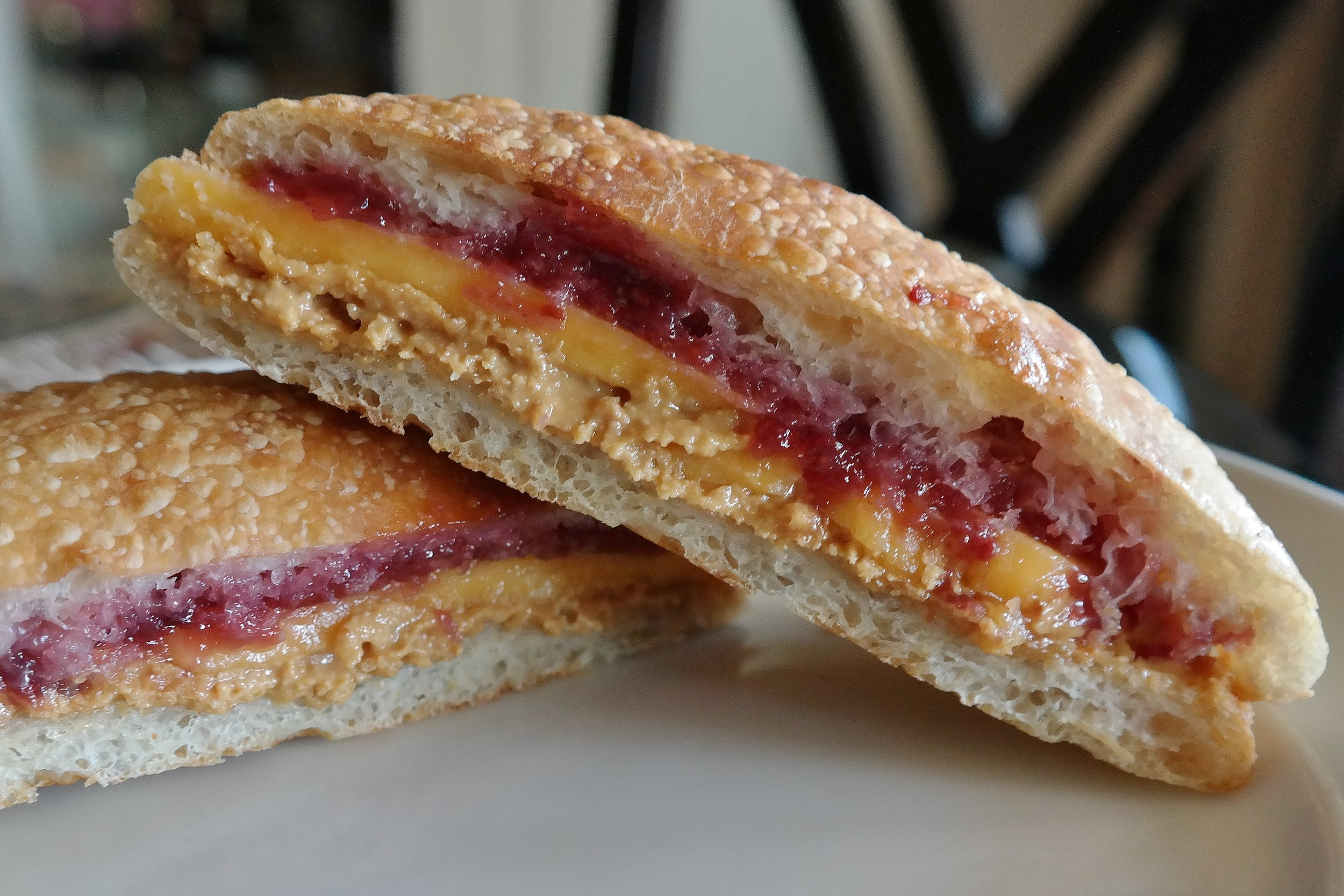 Housemade peanut butter with strawberry jelly and Tillamook sharp cheddar on ciabatta