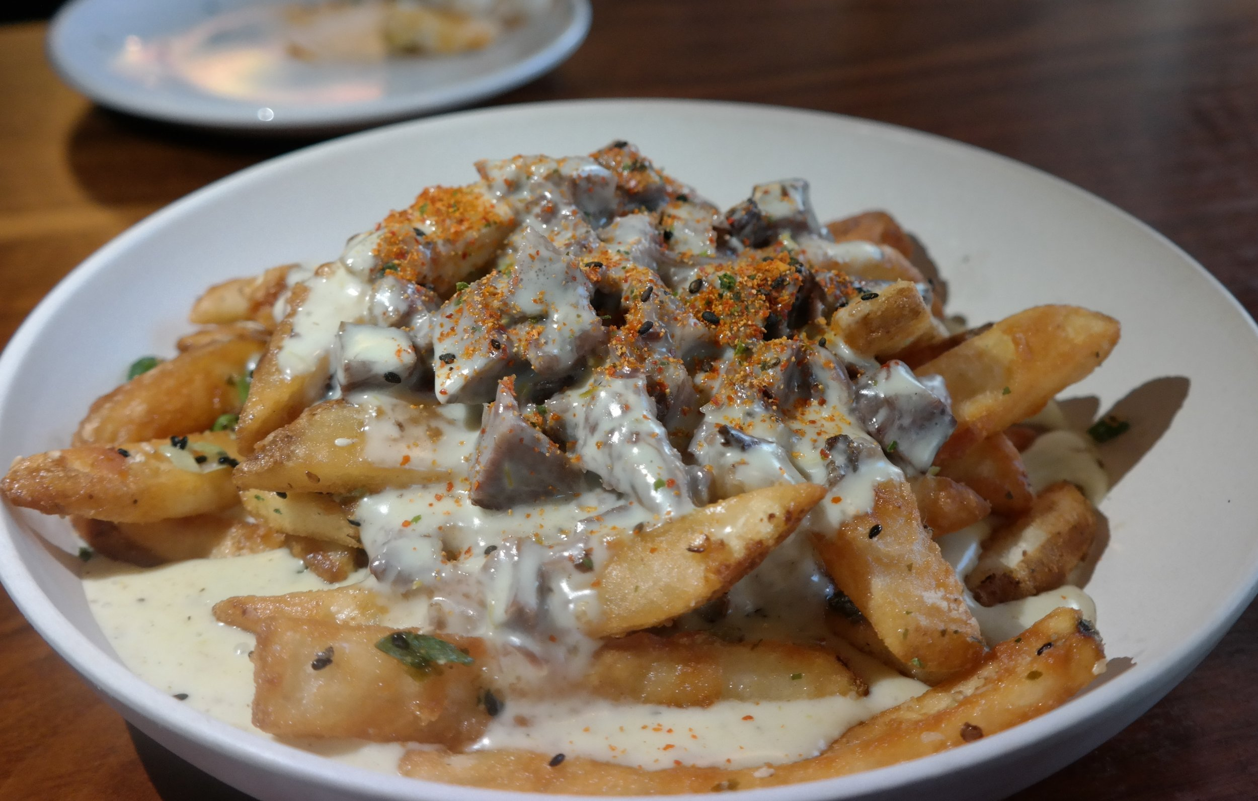 Umami Fries with barbacoa, cheese sauce, and shichimi