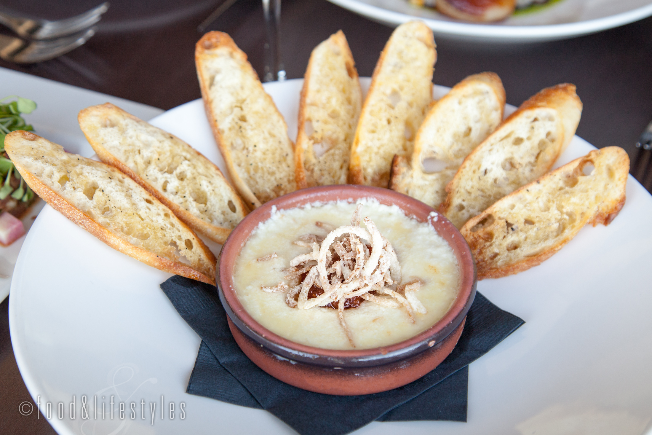 Baked goat cheese fondue with fried shallots and crostini