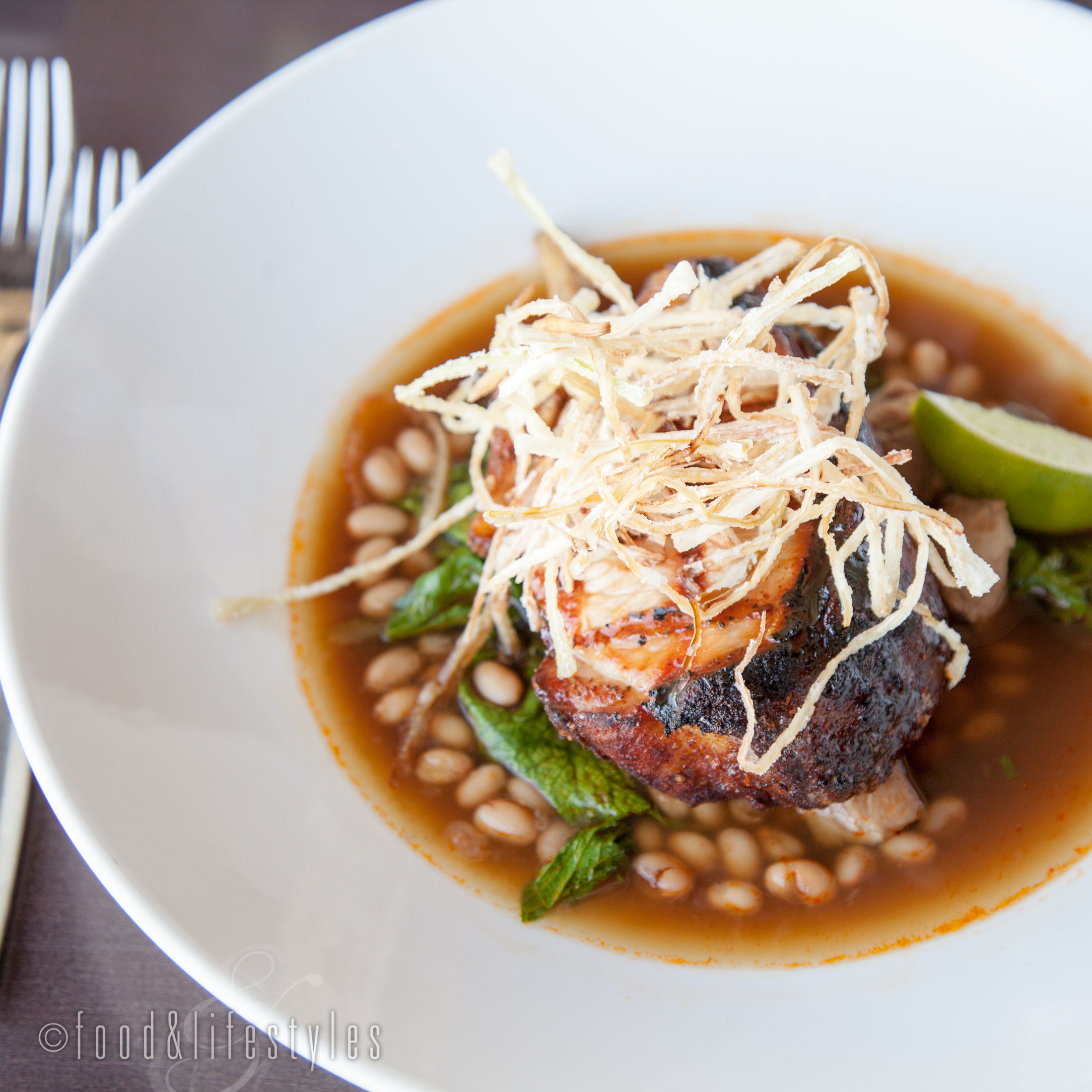 Smoked pork chop with braised white beans and mustard greens