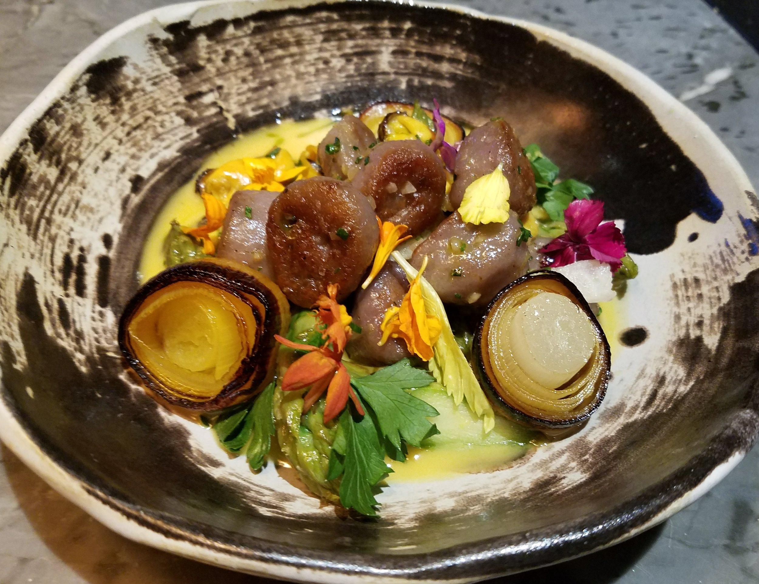 Purple potato gnocchi with saffron-poached mussels, charred leeks, asparagus, and a saffron beurre blanc