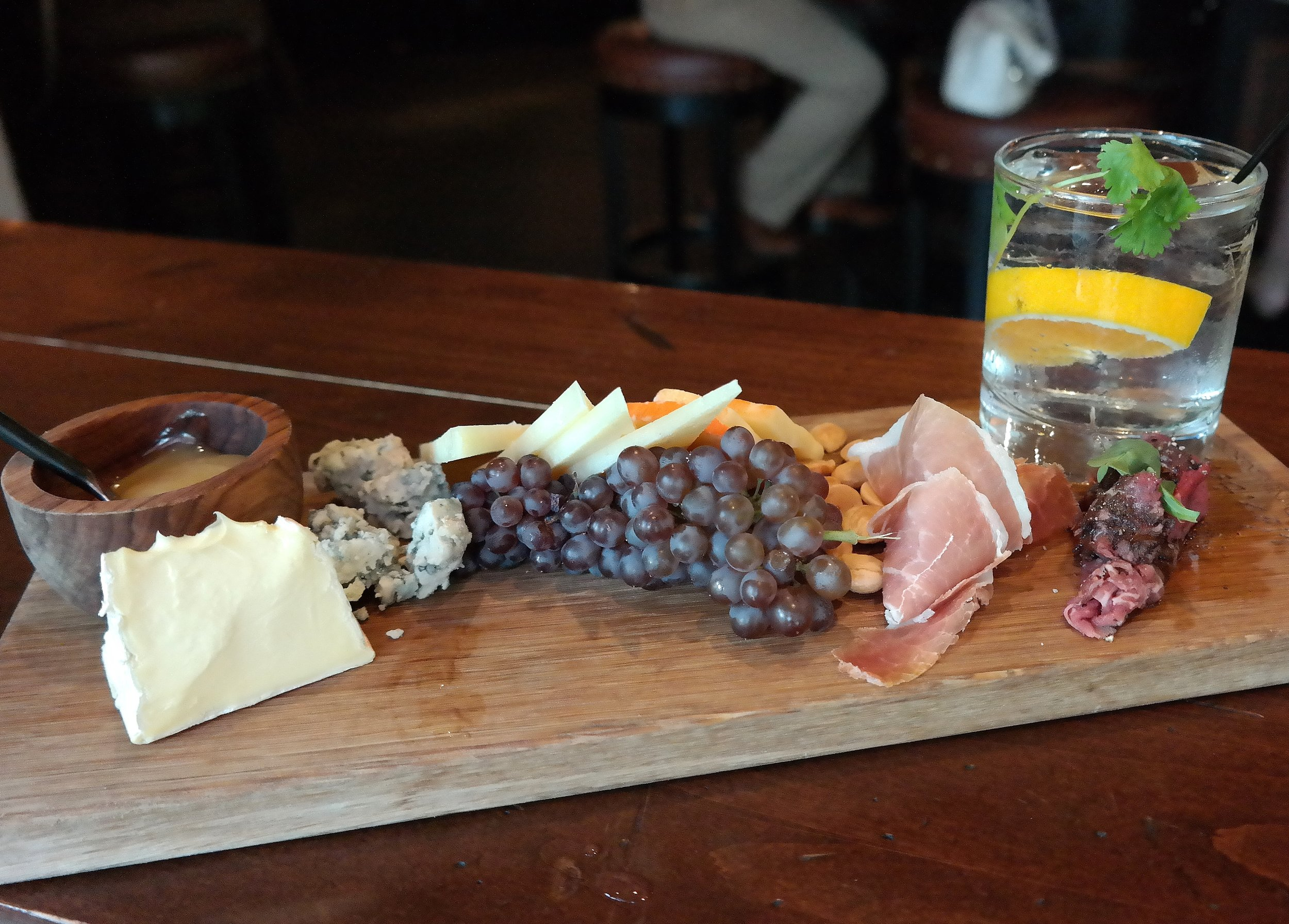Prado's cheese board with Brie,Valdeón, Mahón, and Manchego cheeses, Meyer lemon curd, Marcona almonds, grapes, Jamón Serrano and lomo drizzled with balsamic