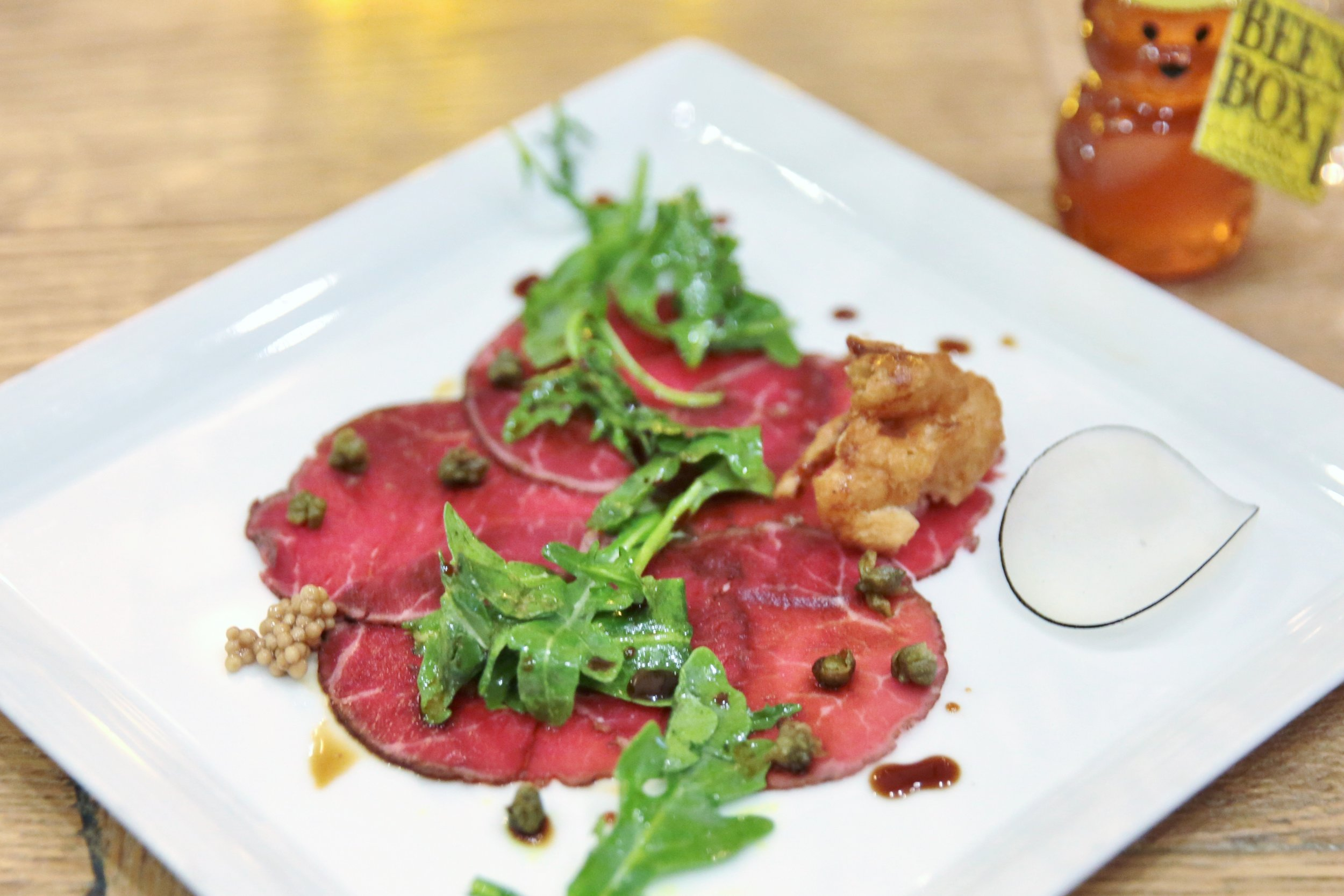 Fourtth course: Arizona Grass-Fed Beef Carpaccio. Lemon, Arugula, and Caramelized Onion Fritter