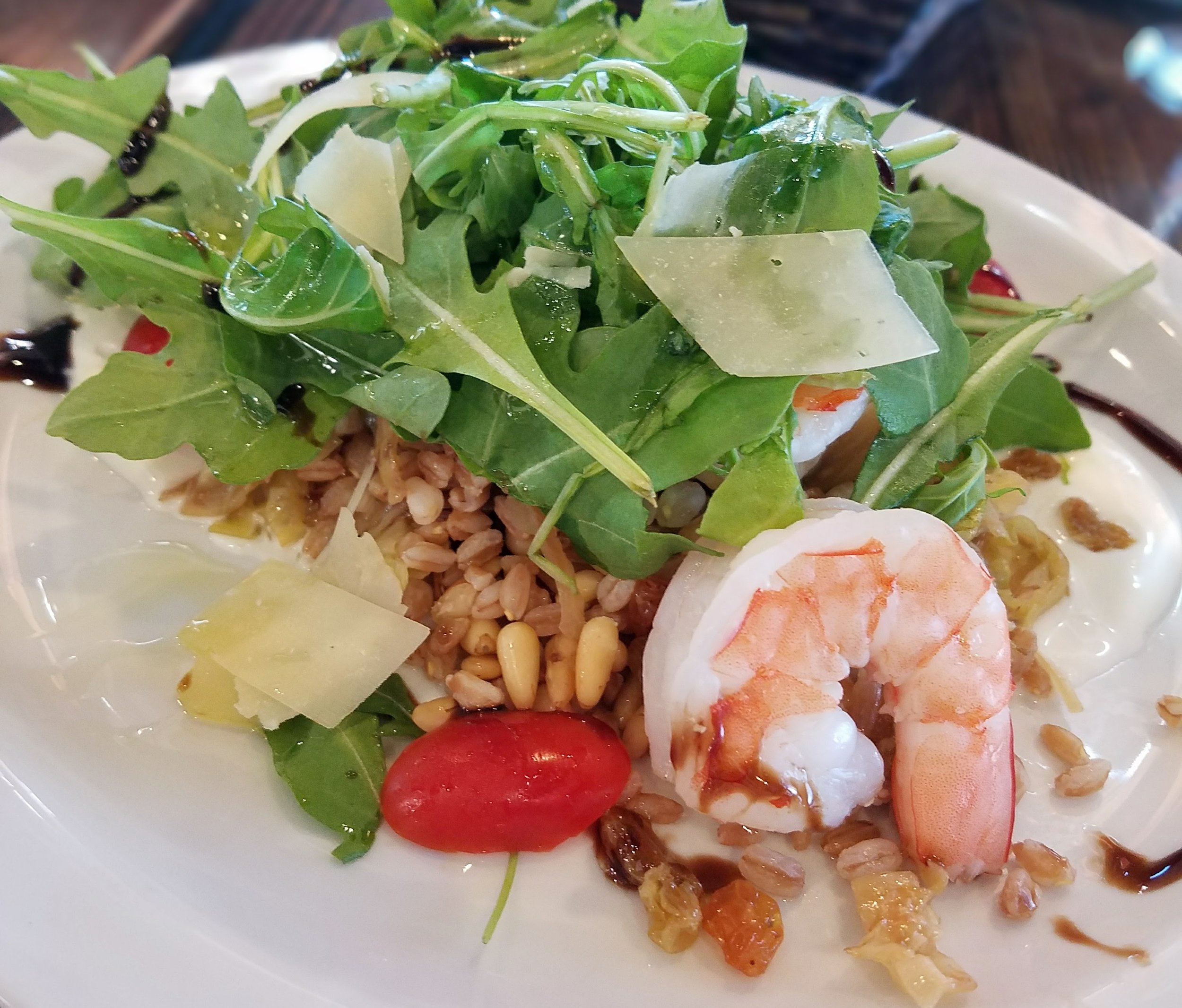 Farro salad with shrimp, golden raisins, roasted pinenuts, arugula and shaved Parmesan cheese