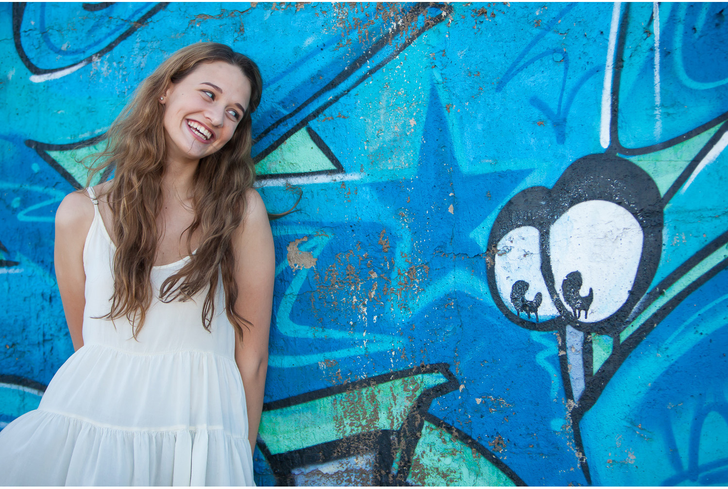 Denver high school senior pictures, gorgeous Maddie smiling at graffiti eyes | photographer Jennifer Koskinen | Merritt Portrait Studio