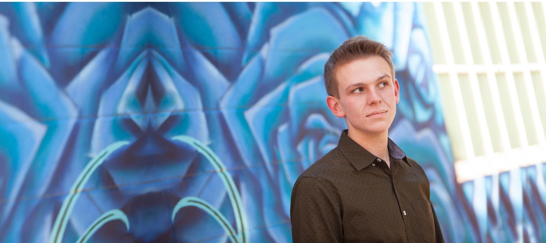 Urban Senior Guy Portraits against blue art wall with Denver Photographer Jennifer Koskinen, Merritt Portrait Studio