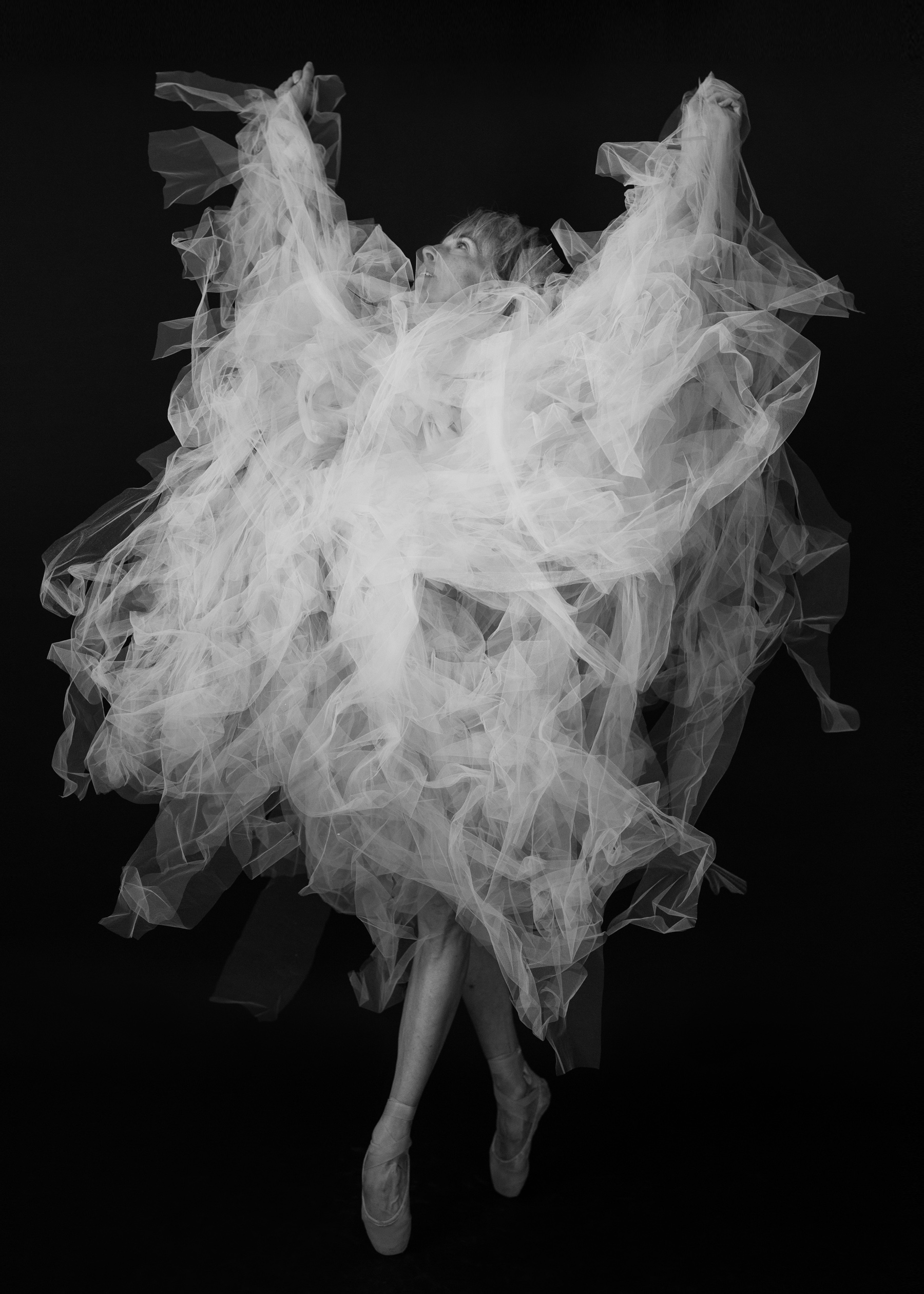 Valerie strikes triumphant pose in flowing tulle during photo session with Denver dance photographer Jennifer Koskinen