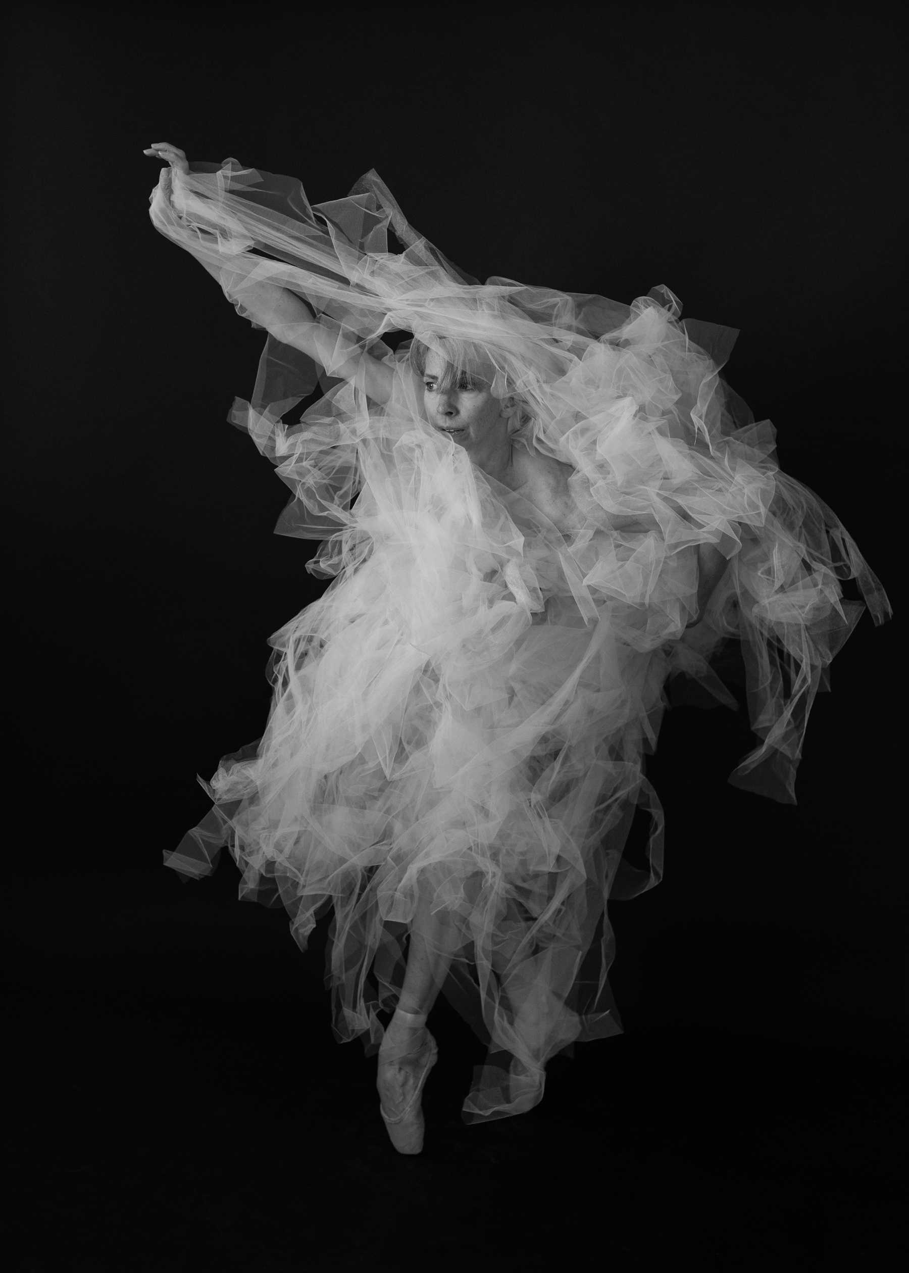 Valerie Madonia dances in flowing tulle skirt during photo session with Denver photographer Jennifer Koskinen, Merritt Portrait Studio