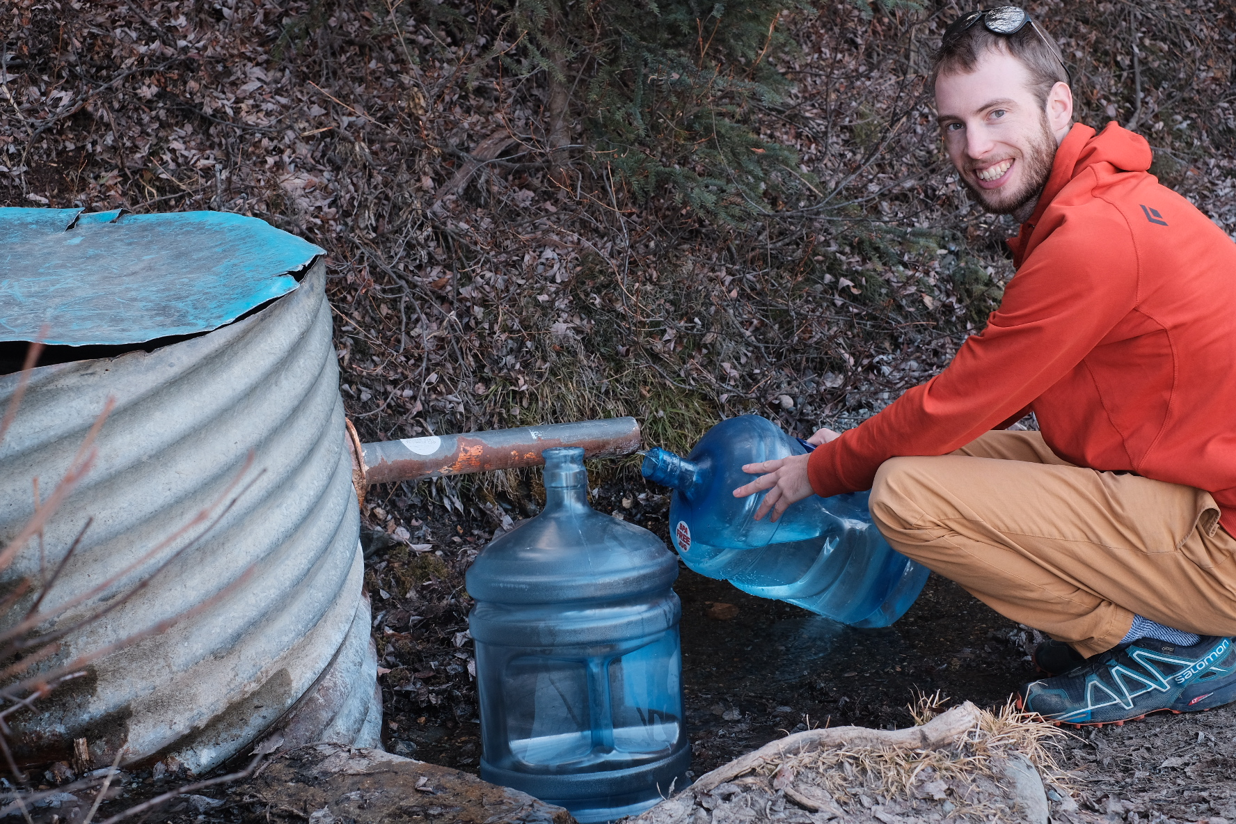 Filling blue water jug at a creek. Such is the hippie life.