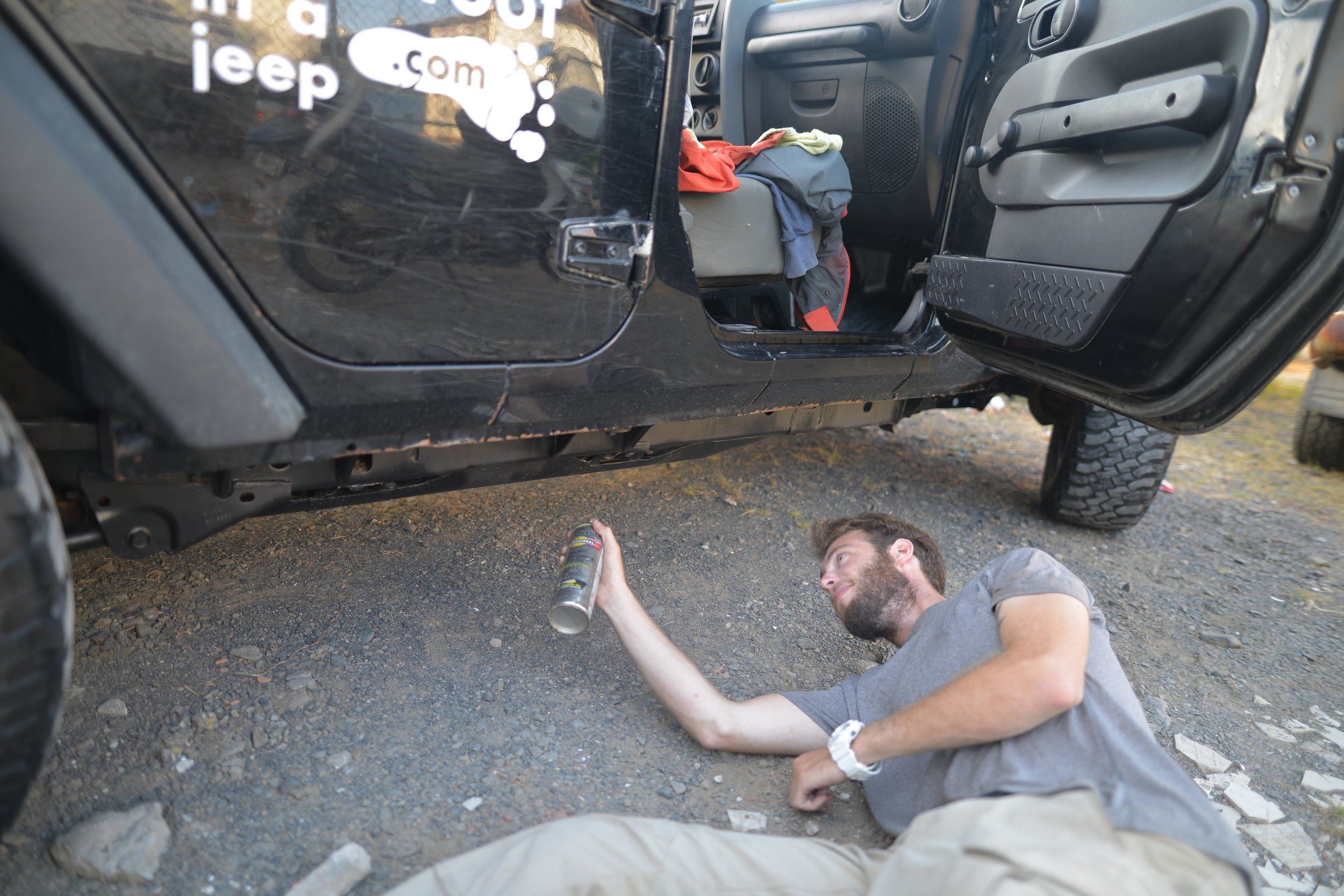 Spraying the bottom of the Jeep with a rust-proof black paint.