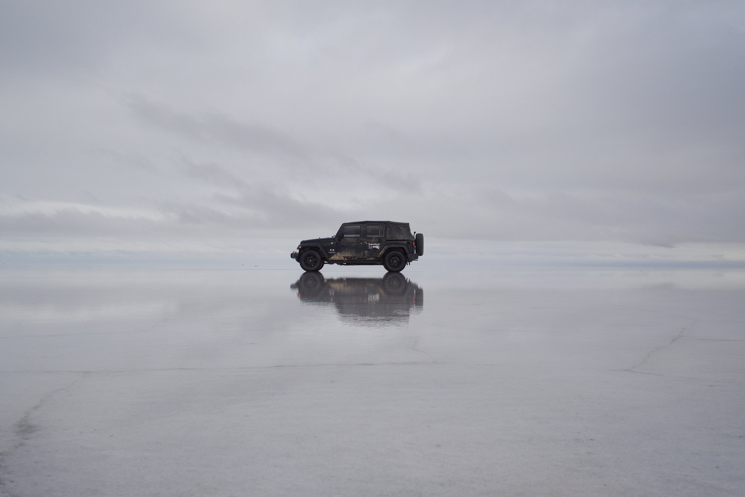 The Jeep in the largest salt flats on Earth: Uyuni in Bolivia.