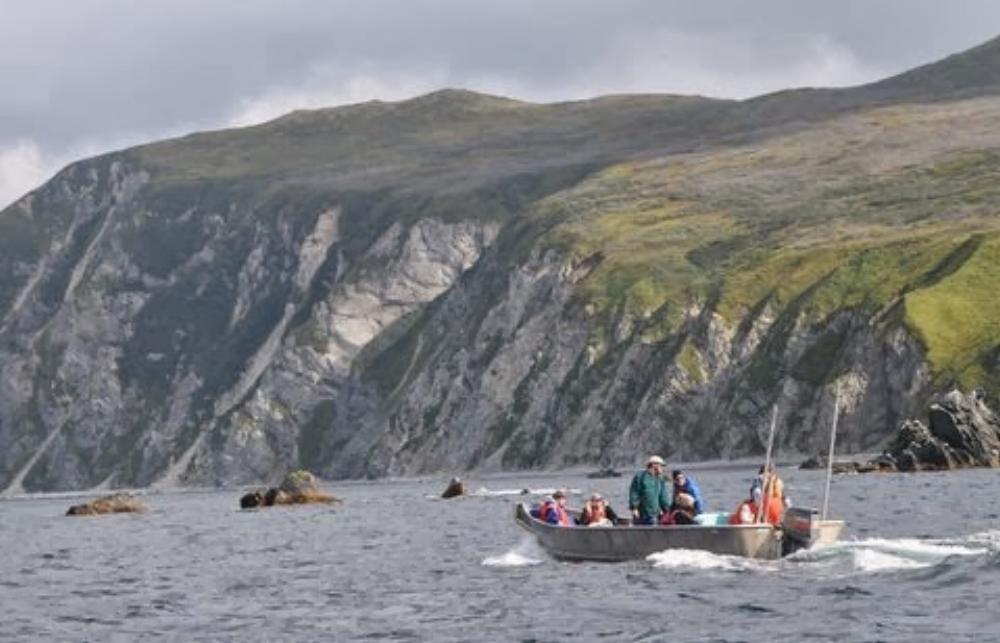 HIWW skiff and cliffs.jpeg
