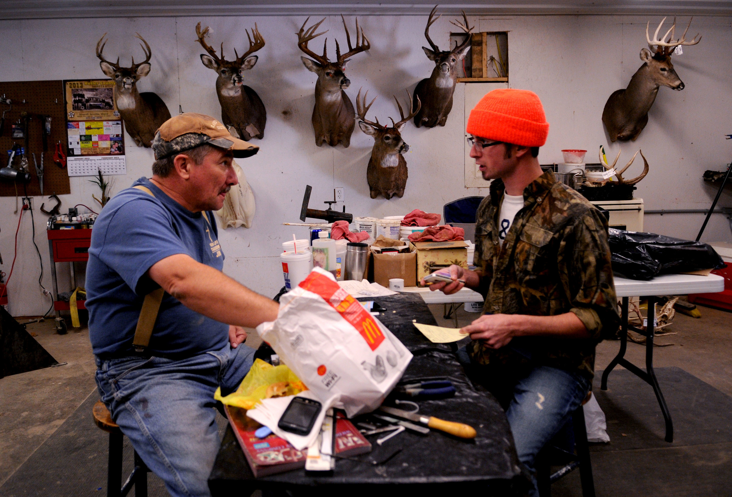 Jim McIntosh (left), of Morgantown, Kentucky, eats lunch and talks with customer Justus Eaton (right), on Friday, November sixteenth, about the specifics of what kind of deer mount he would like. Eaton traveled from North Carolina specifically to hunt deer in Kentucky.