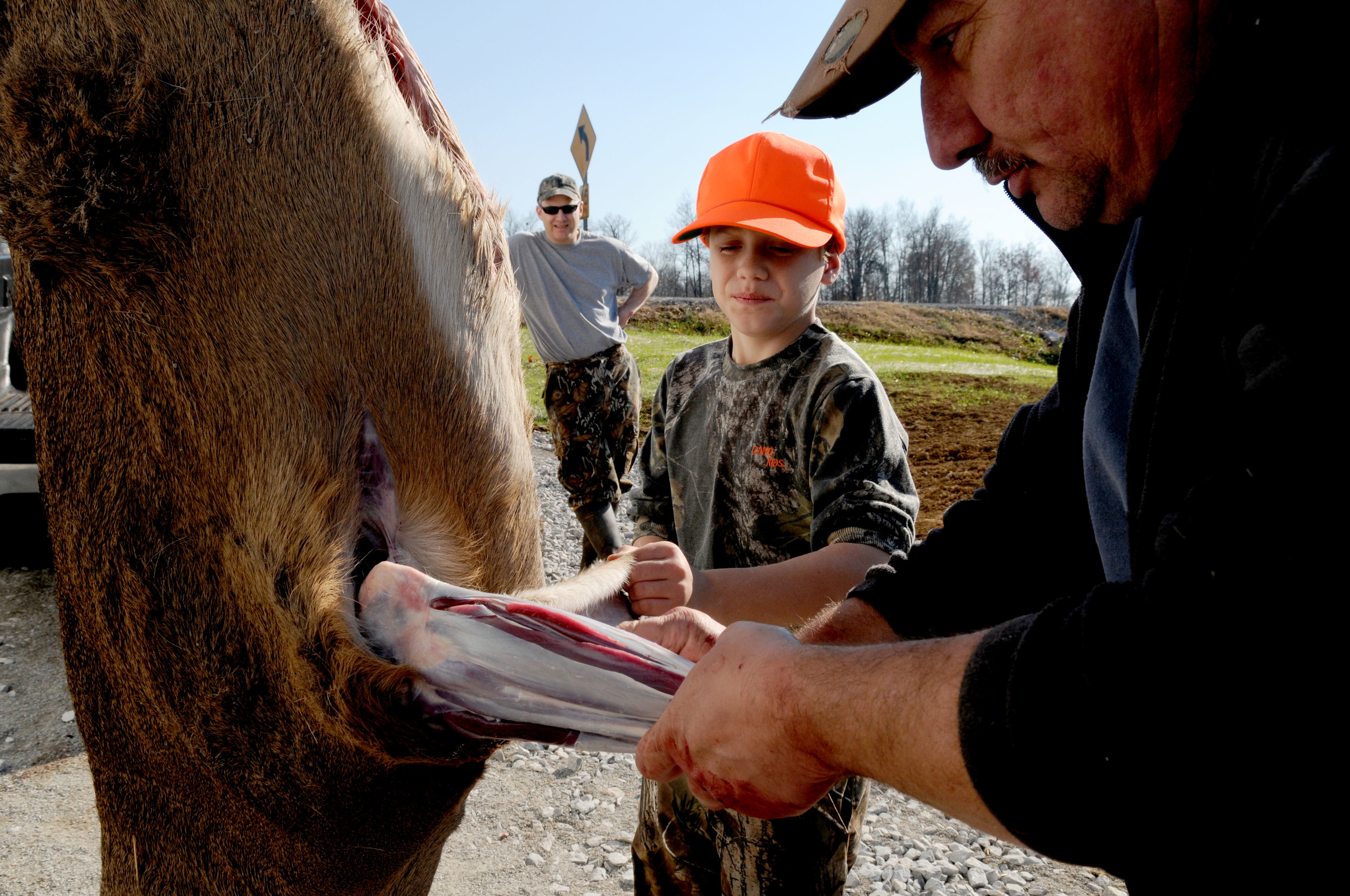 Bob McPherson (left) watches as his son Andrew, 10, (center) helps Jim McIntosh (right) skin a deer that Andrew shot earlier that day outside 'Jims New Life Taxidermy' on Friday, November sixteenth. This deer, which was Andrews first ever, will be prepared for a wall mount by Jim within the next six months. McPherson and his son traveled from Virginia to hunt in Kentucky.