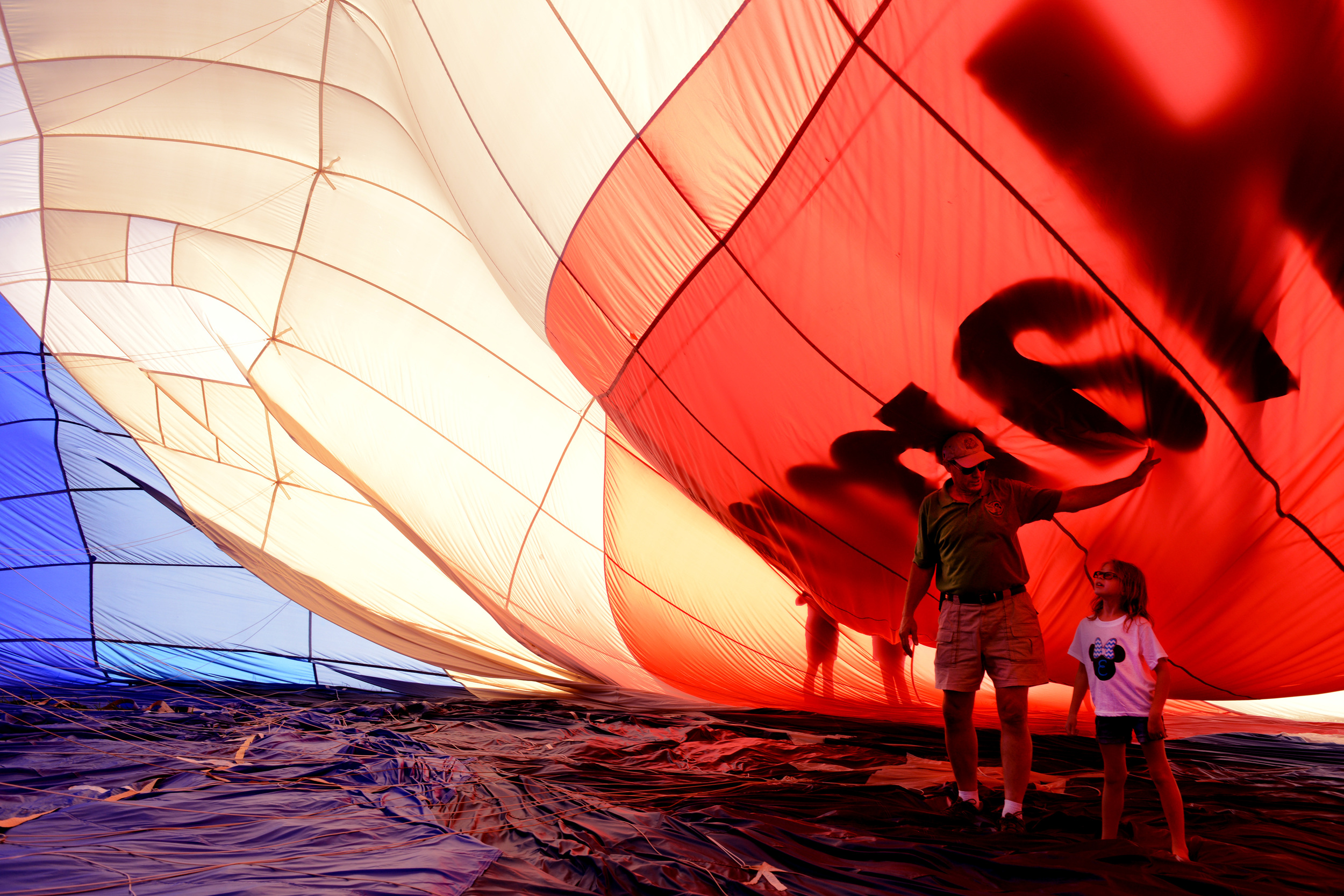 Bill Smith, left, shows Emily Meadows, right, what the inside of his 90,000 square foot hot air balloon, named Aero Force One, looks like before he puts it into storage after the 2014 Balloons, Tunes and Barbecue Festival, at the Bowling Green Airport, Friday, Sept. 5th.