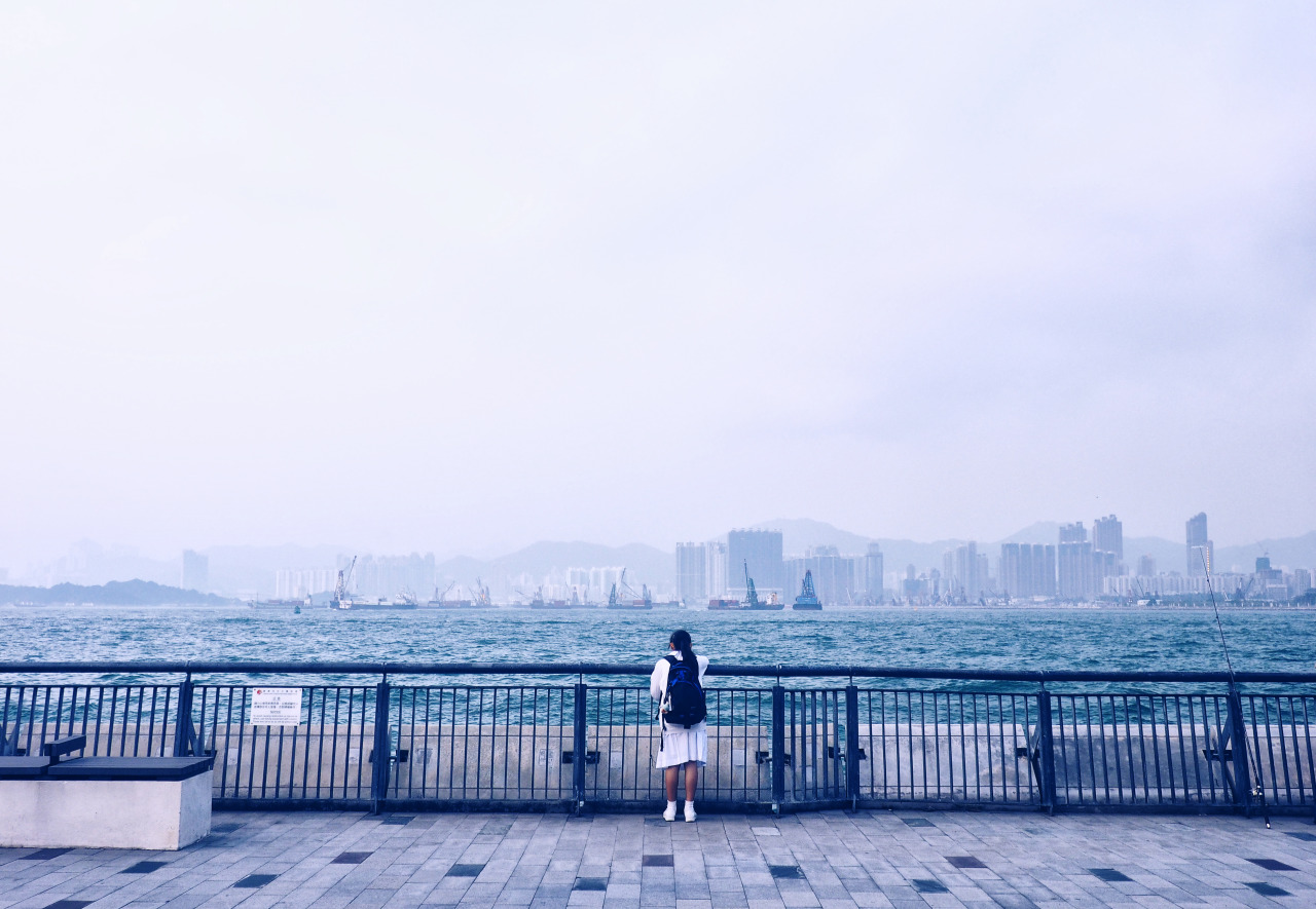 She didn't move for over an hour and stood there looking at the water with her headphones on. I tried to get her attention but realised she was in her own world and I didn't exist.    Sun Yat Sen Memorial Park Promenade, Hong Kong.      Olympus OM-D E-M1 + 12-50mm f/3.5-6.3