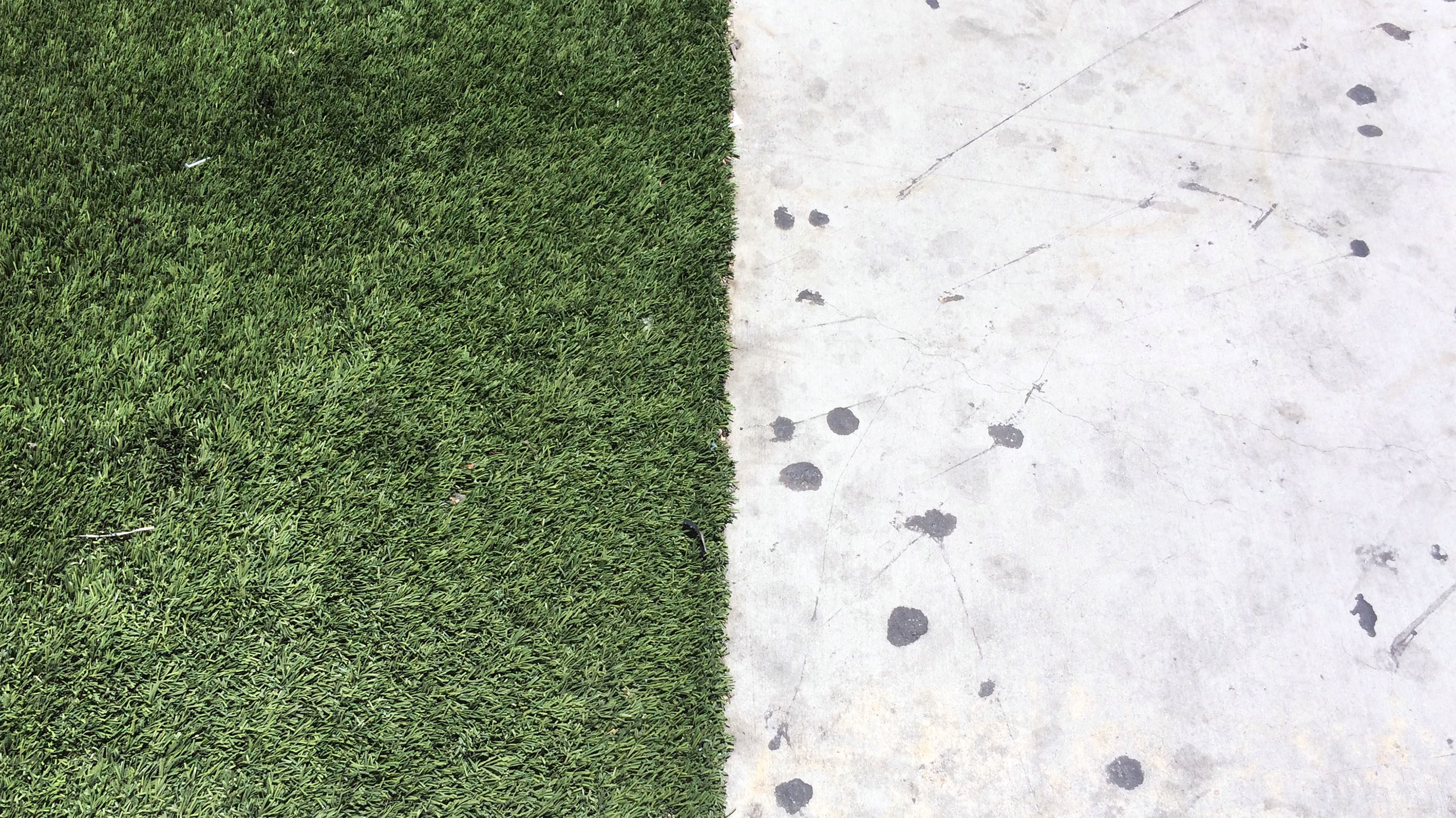 A hard divide between concrete and synthetic turf on a sidewalk on Los Angeles Street in the Skid Row neighborhood of Downtown Los Angeles. (Photograph by Ian Besler)
