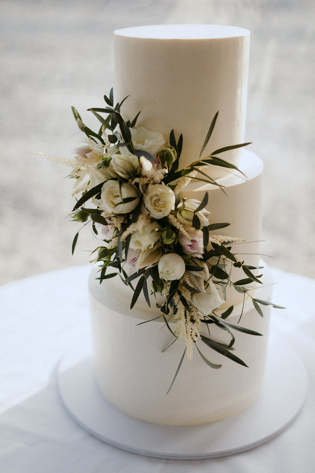 The chocolate mud cake had 3-tiers and a simple design. White buttercream icing was adorned with florals.