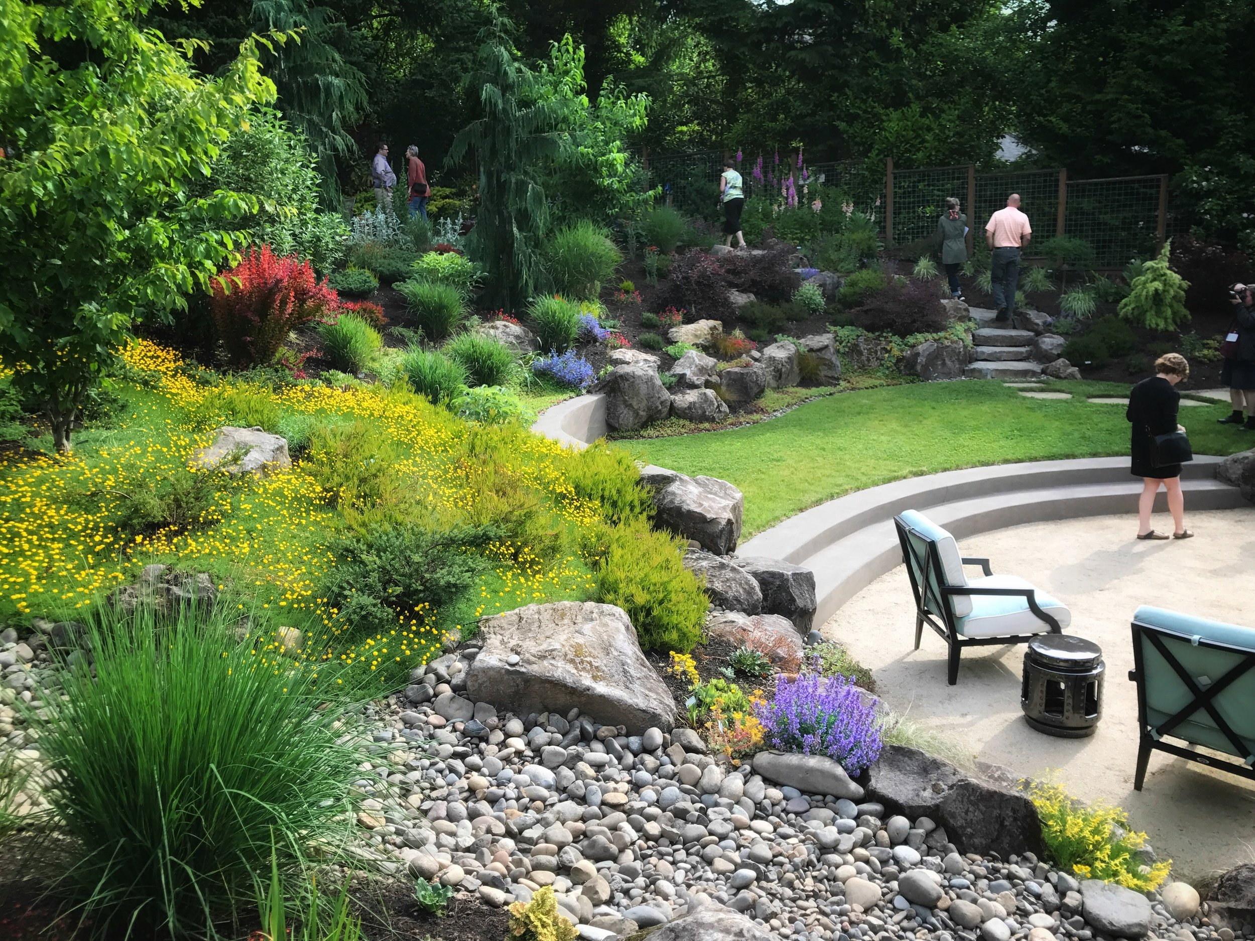 Amphitheater effect, perfect aspect to look up into from patio below. Effective plantings by Hardiman & LaTourette and homeowners. Landscapes East & West installed the beautiful concrete from the designer's work.