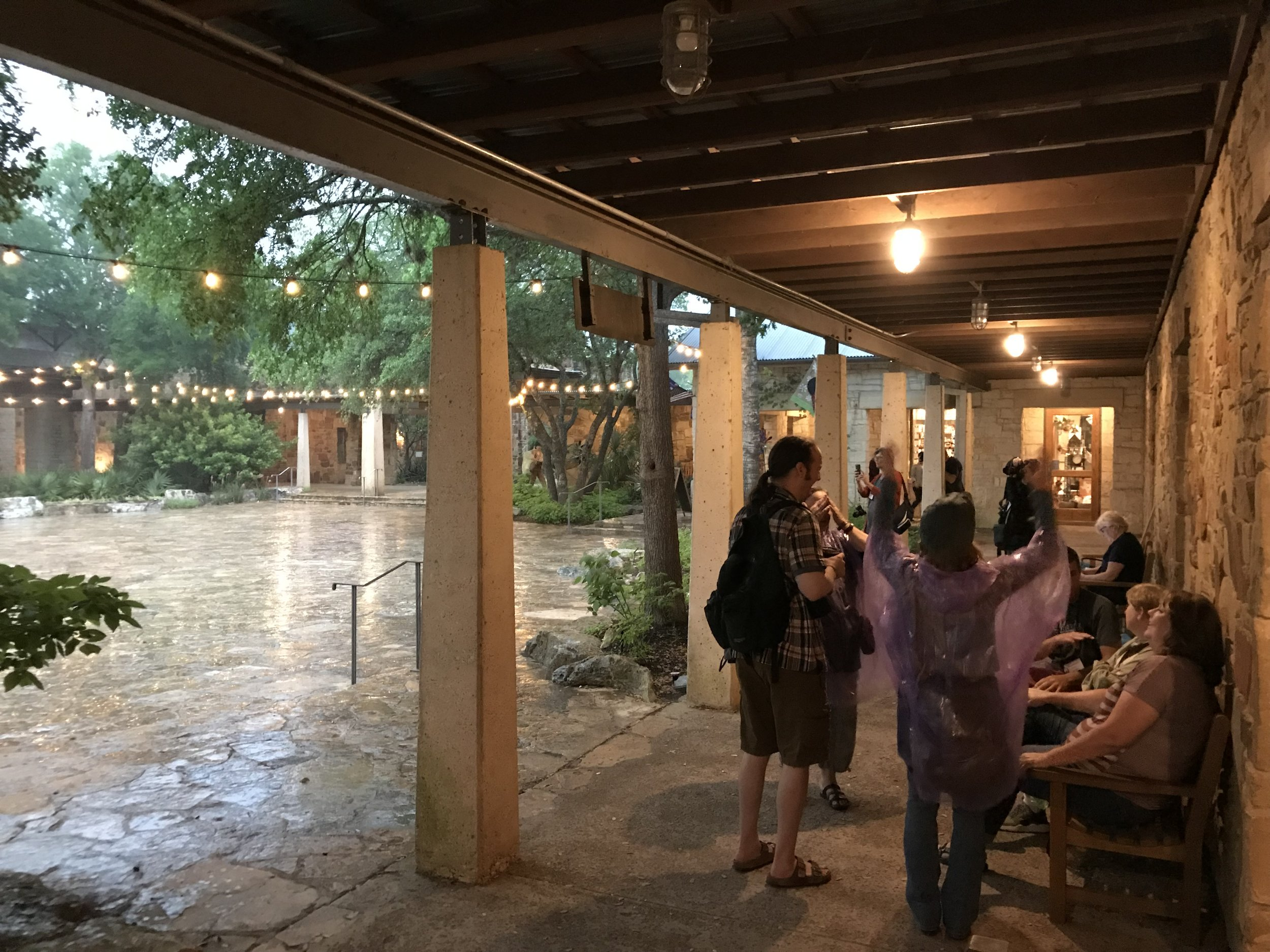 Our group seeking shelter from the rain, under the central courtyard's porticos.