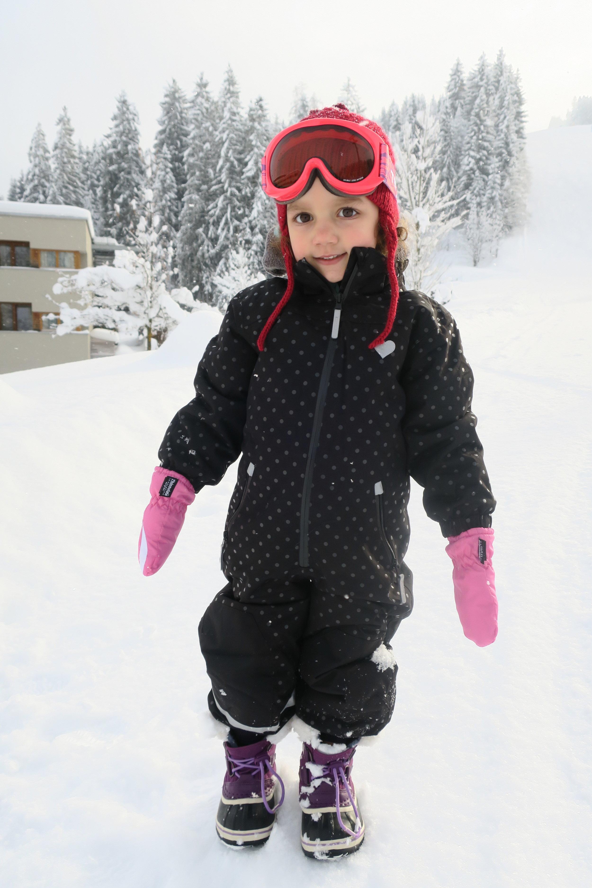 Olivia equipada para brincar na neve e o hotel no fundo