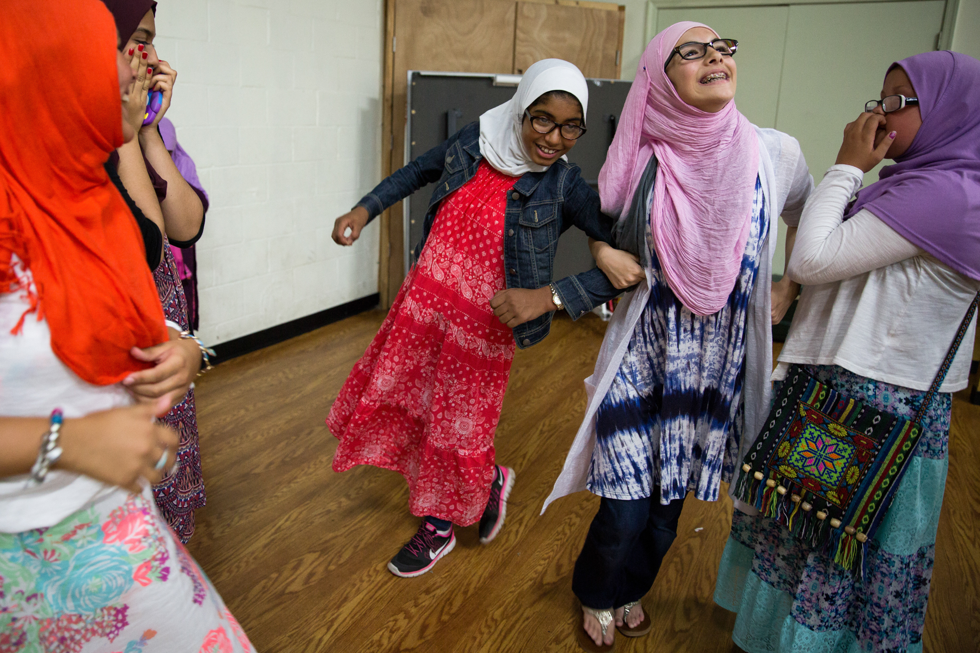 Zaineb, center, and Aisha Taghi, right, laugh and link arms during an event at the Masjid. Most of the girls go to different schools and only get to spend time together as a group at events organized by their mothers.