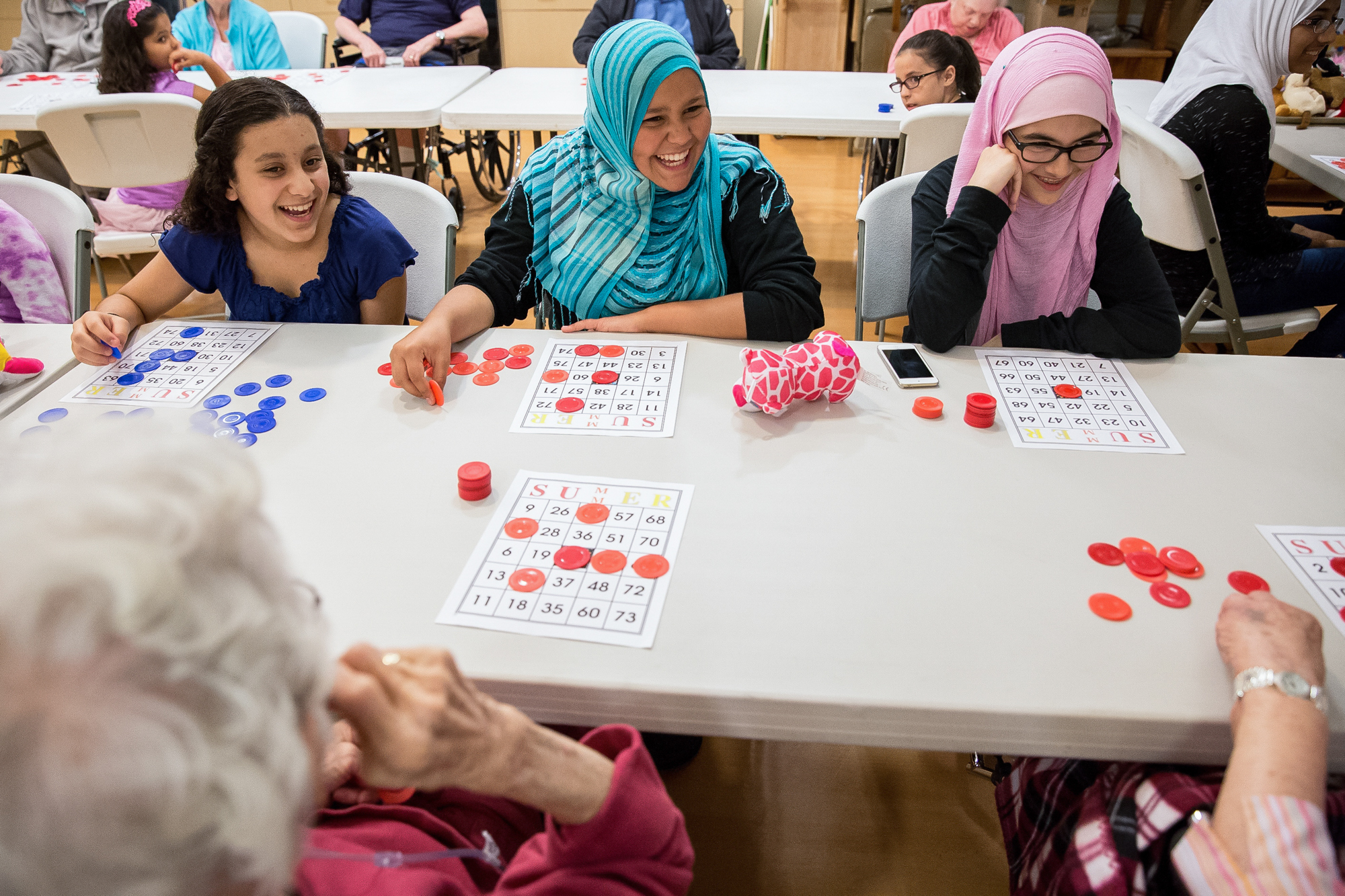 From left to right, Leila, Ayesha and Aisha play bingo with residents at Bethany Village in Mechanicsburg. The girls visit and participate in activities with the residents at the nursing home twice a month as part of their group, Dawah in Action.