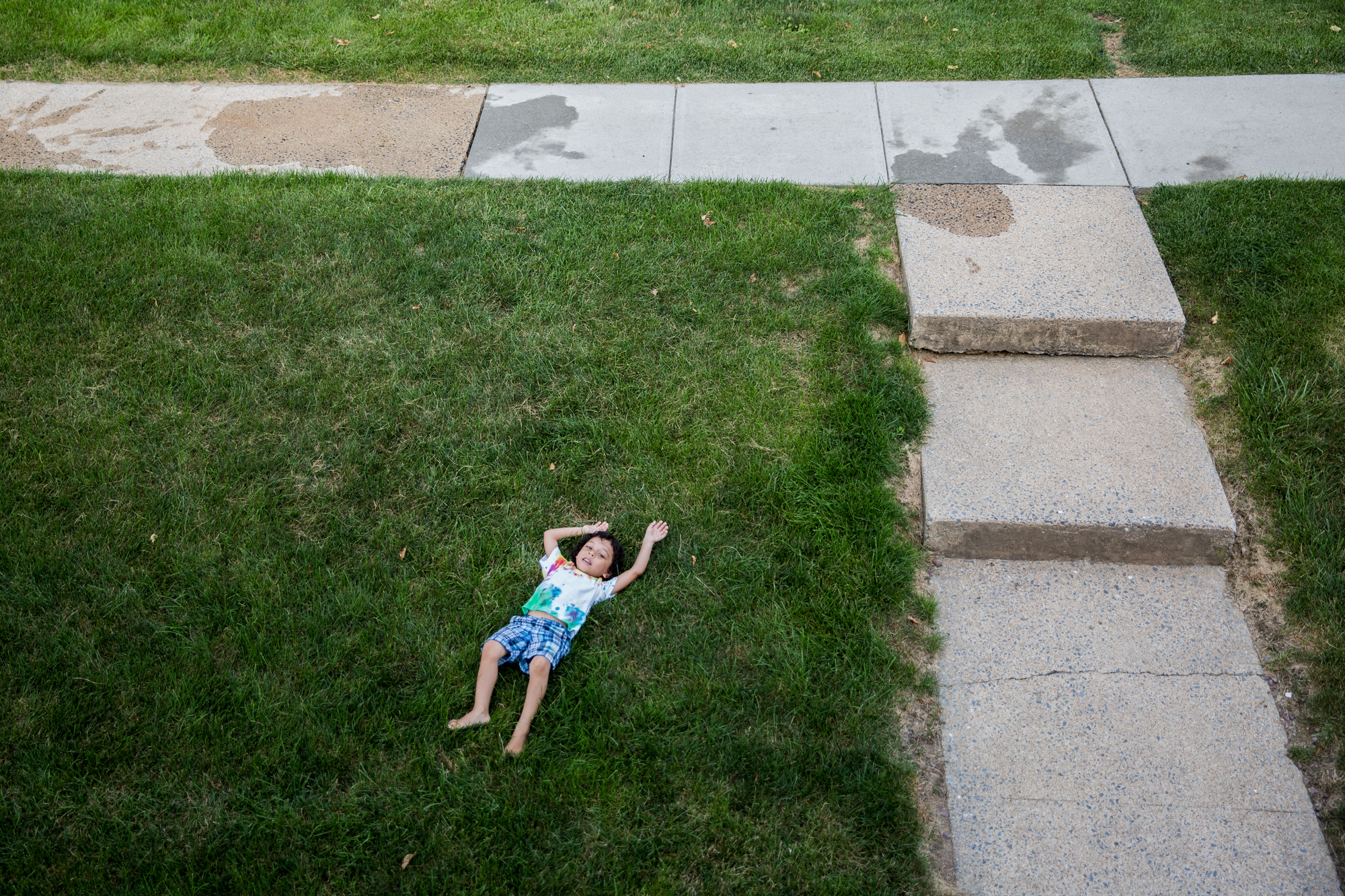 Gamal lies in the grass after a water balloon fight with his sister outside of their apartment in Camp Hill.
