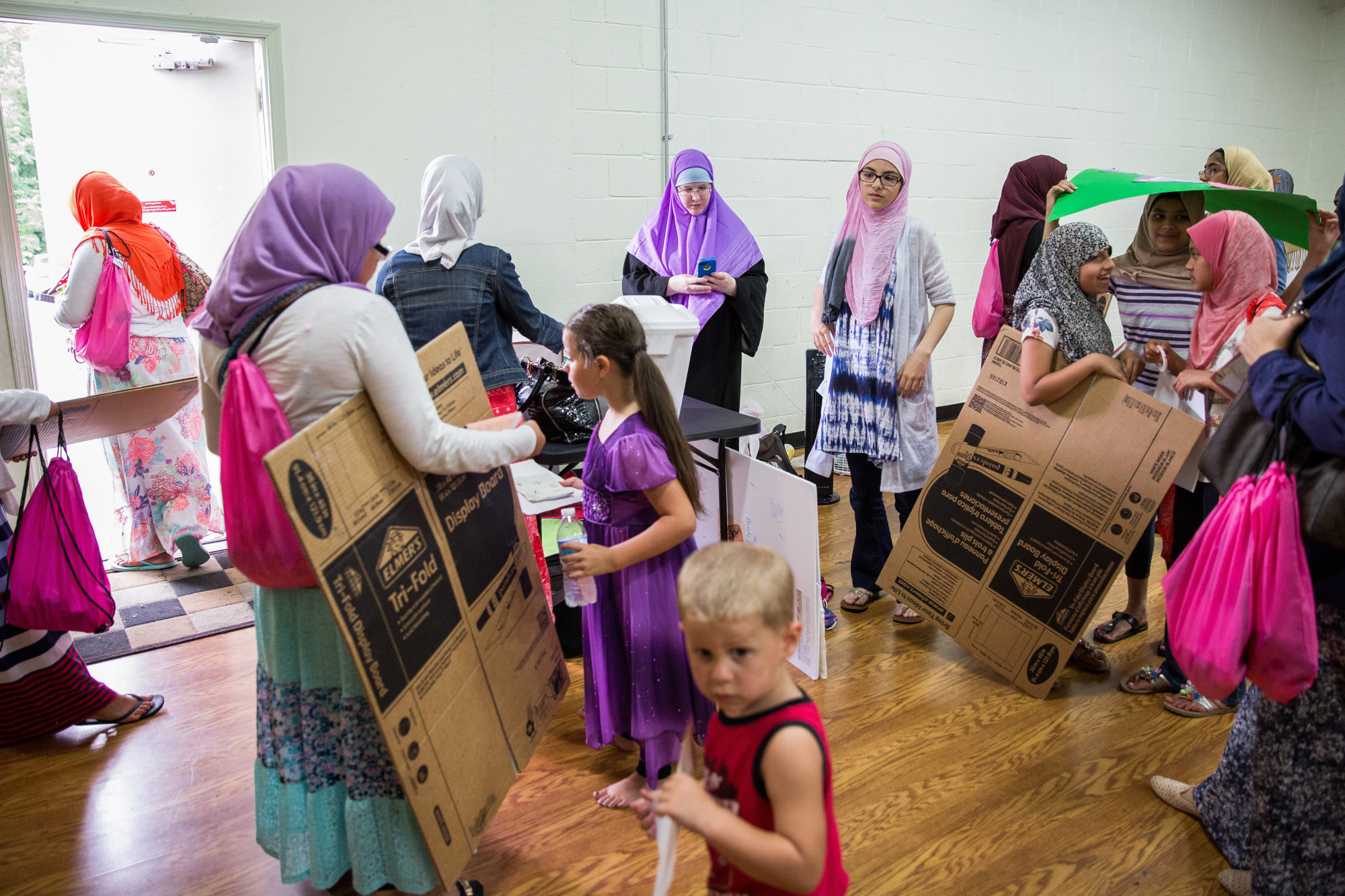 Girls carry poster boards and projects about Muslim inventors after an event at the Masjid in Mechanicsburg. Kareema organized the event as a way for the girls to learn more about their heritage and to help instill a sense of pride about being Muslim.