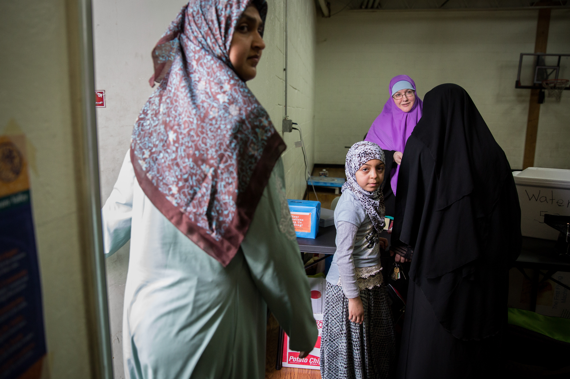 Malik, center, waits patiently to leave as her mother talks to Kareema after an event at the Masjid in Mechanicsburg.