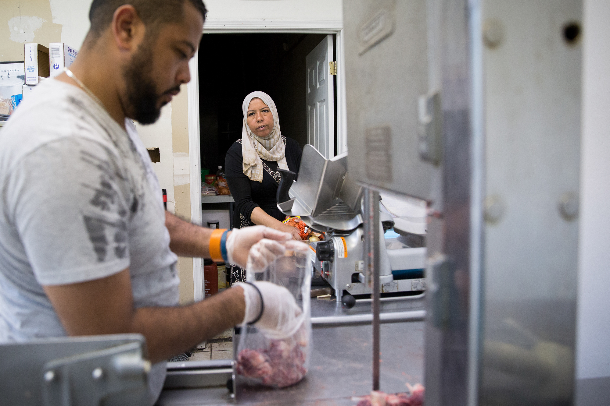 Ola Soweilam talks to her brother, Ahmed Soweilam as he packages meat at El Ola Mediterranean in Camp Hill. Ahmed helps his sister at her store most days of the week, often serving customers while Ola works in the kitchen.