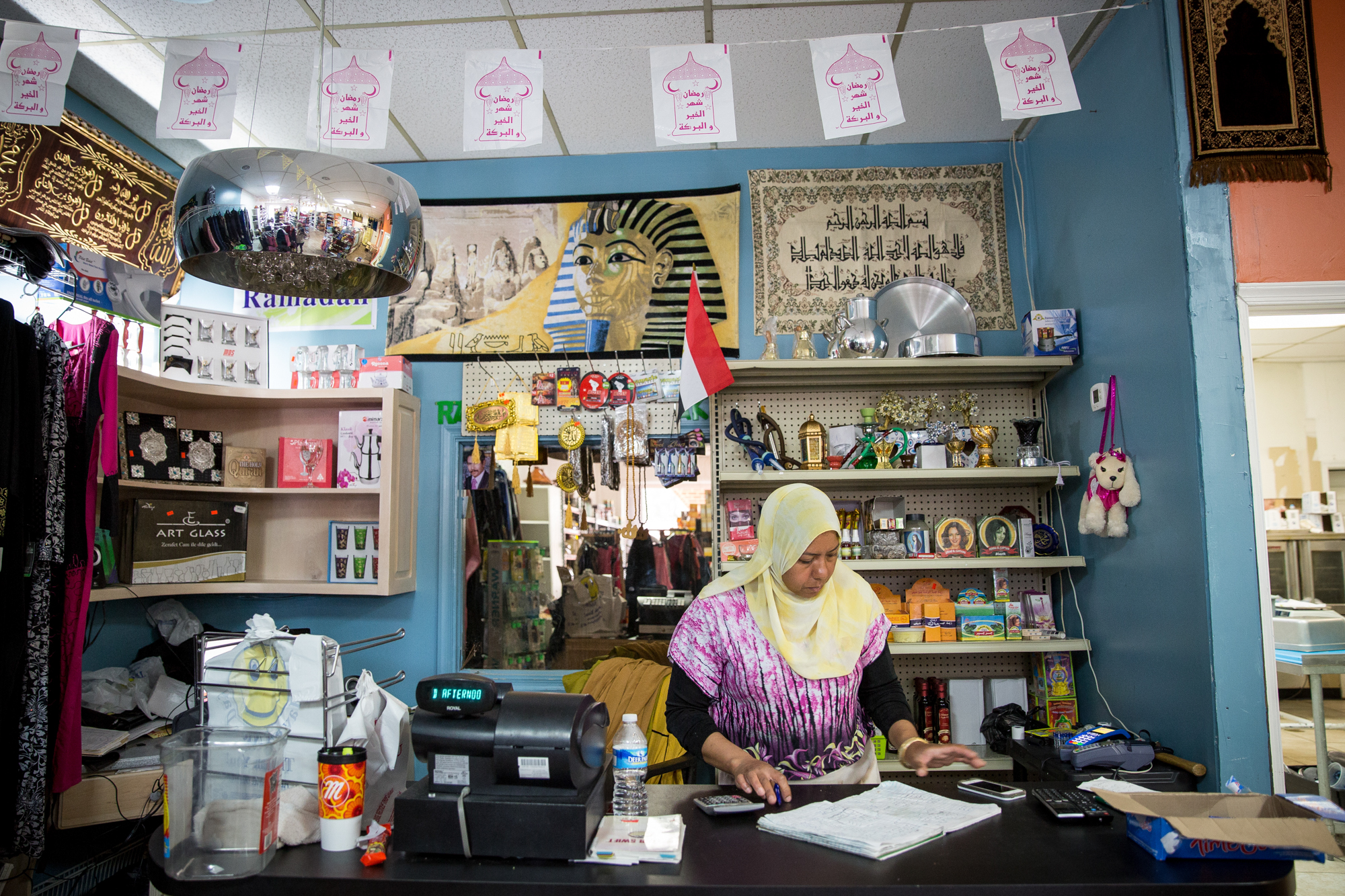 Ola processes payments at her store in Camp Hill, one of the few in the area that specifically serves people from the Mediterranean and Middle East. Ola owns the store and works long hours to keep it running nearly every day of the week.