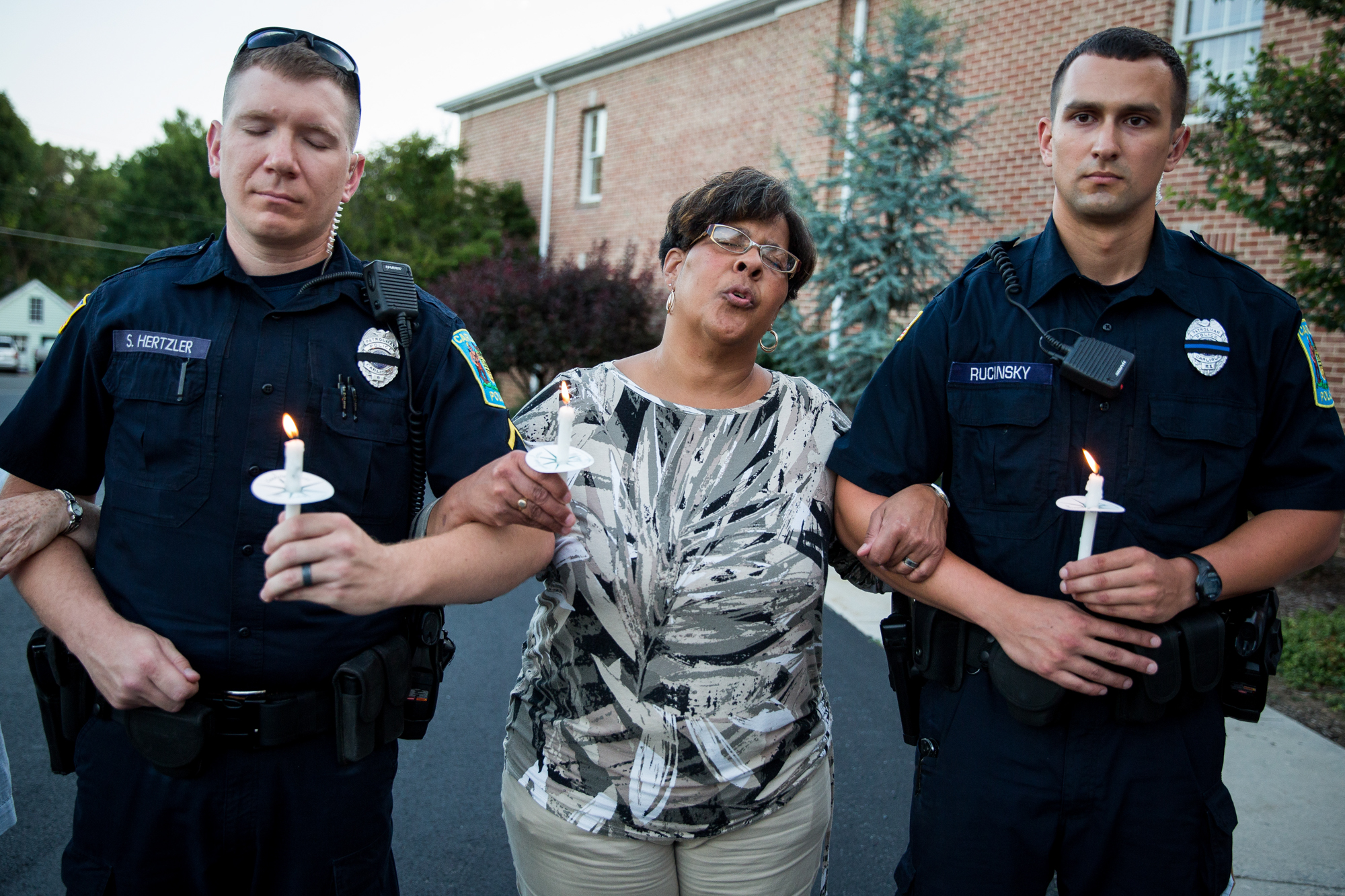 Linda Manning, center, links arms with Officer Scott Hertzler, left, and Officer Joe Rucinsky, right, during a candlelight vigil for victims of police violence and for the five Dallas police officers killed during the summer. A group from Carlisle, Pennsylvania, gathered in remembrance at the local YWCA on July 15, 2016.
